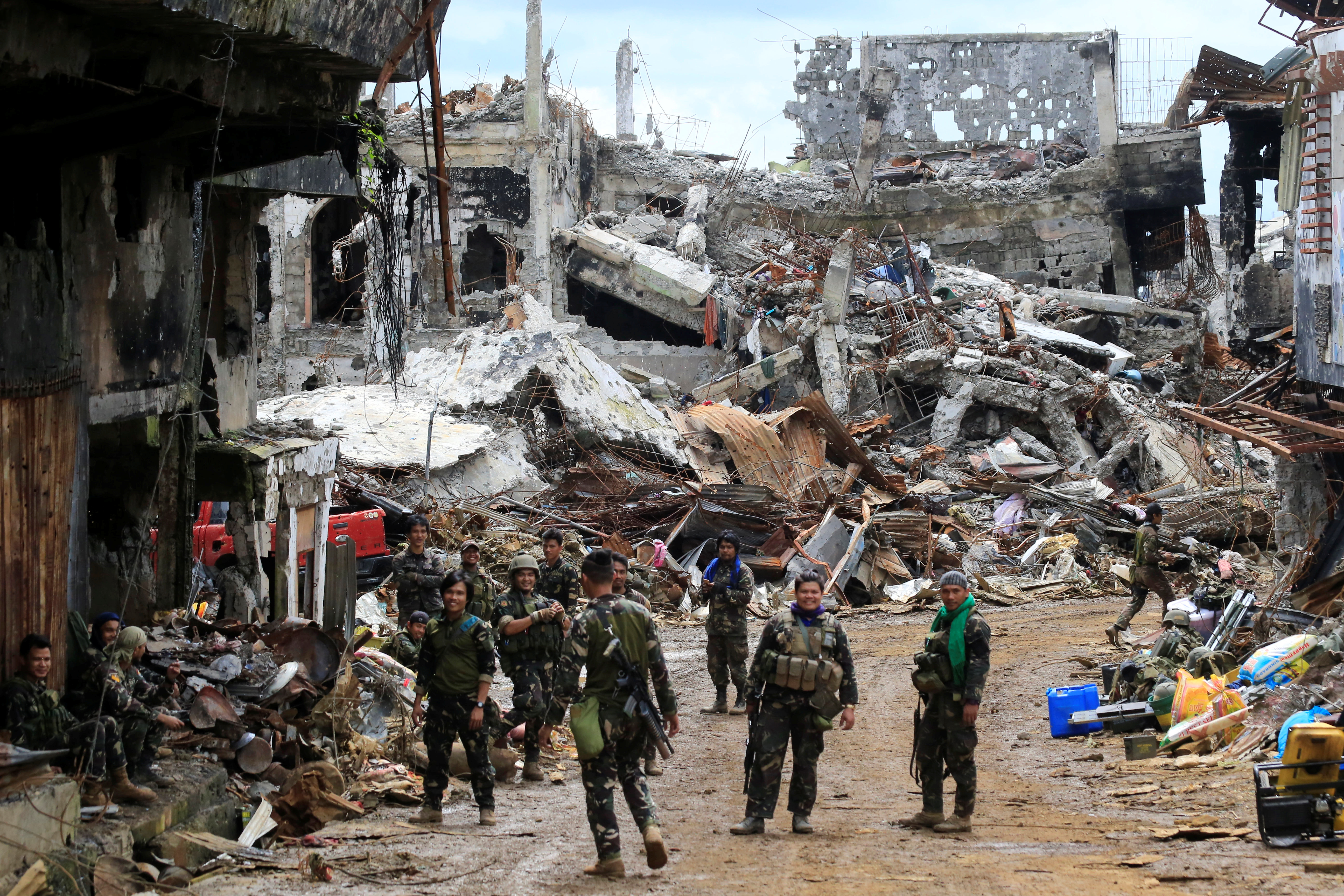 Government soldiers stand in front of damaged houses and buildings in Marawi city, Philippines, October 25, 2017.