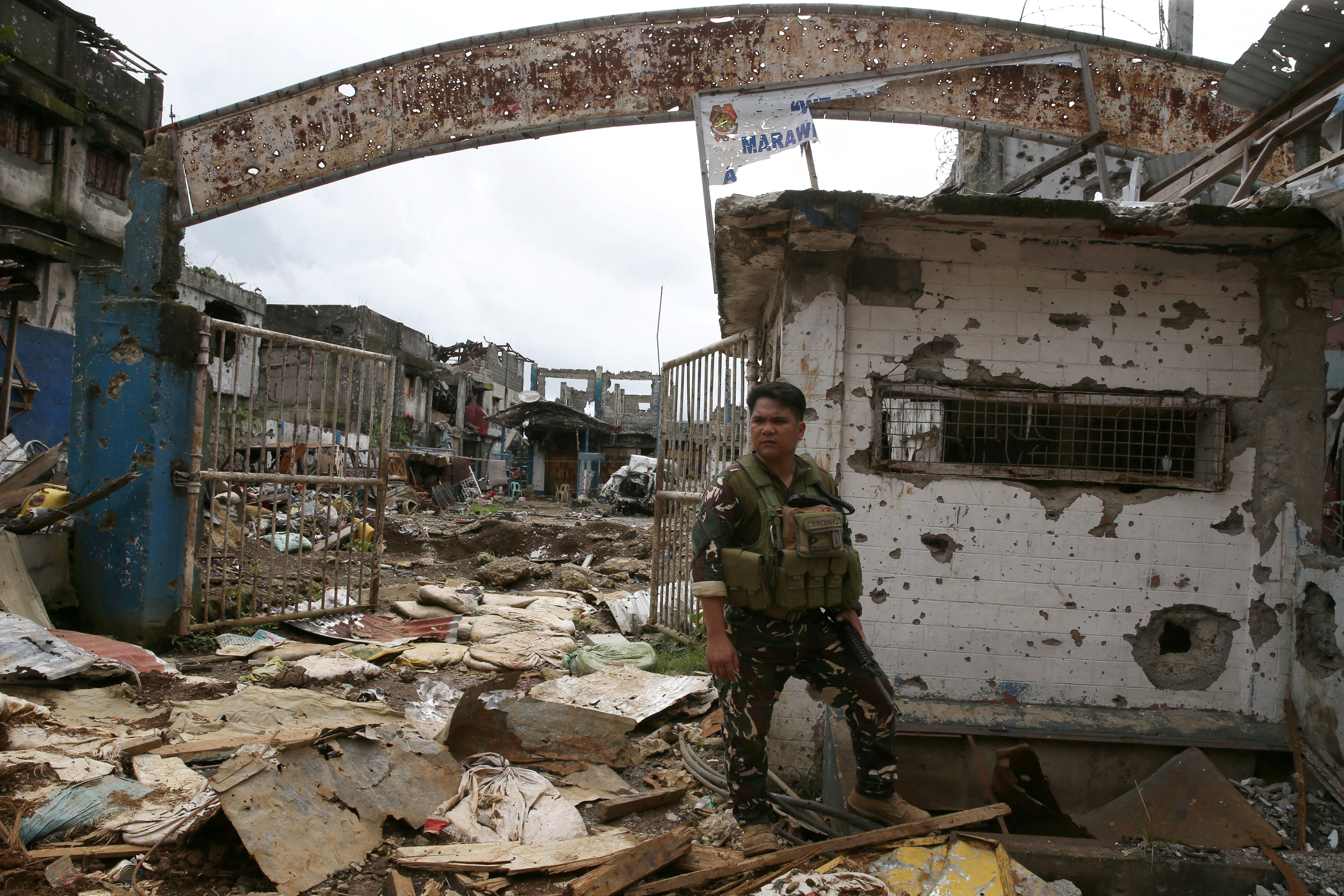 A government soldier stands guard in front of damaged buildings in Marawi city, Philippines October 25, 2017.