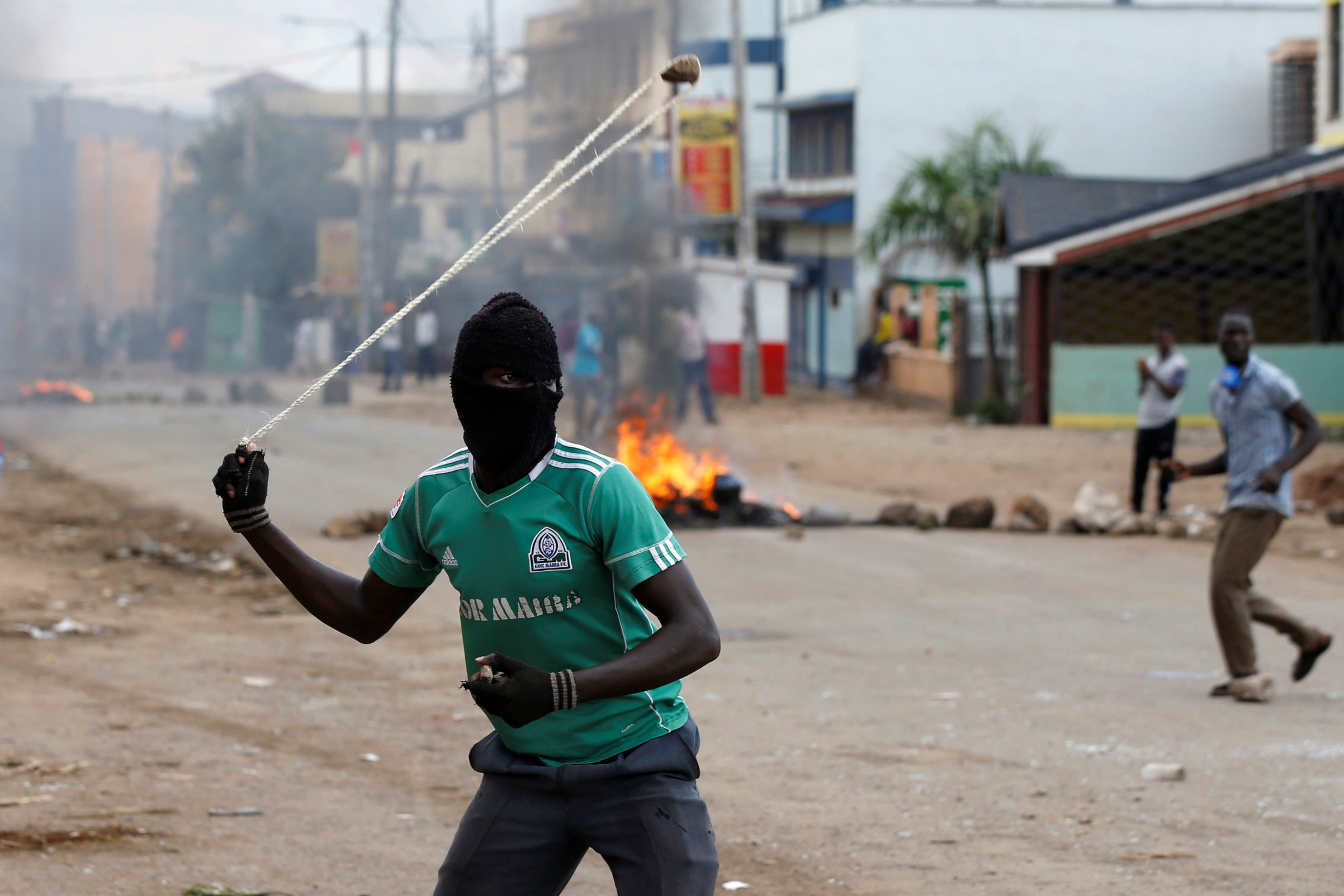 A supporter of Kenyan opposition leader Raila Odinga throws stones during a protest in Kisumu.