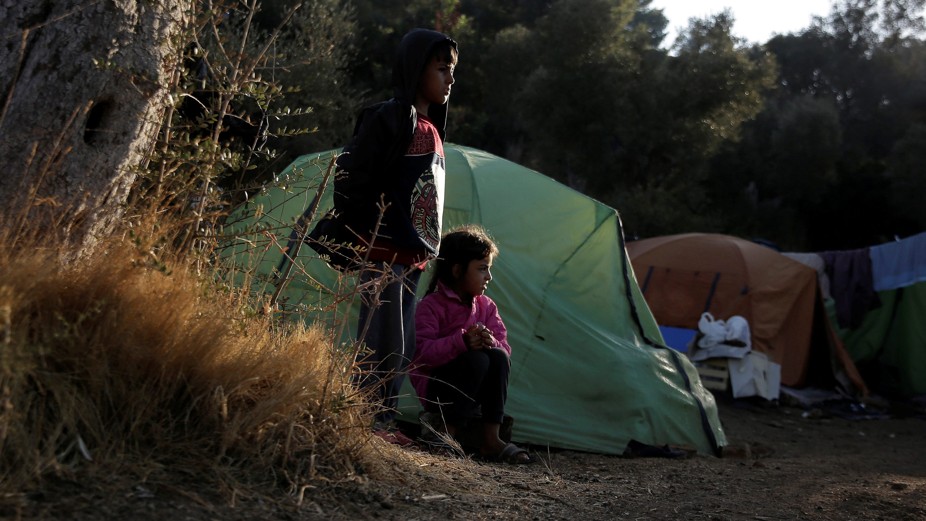 Children look on at a makeshift camp on the Greek island of Samos