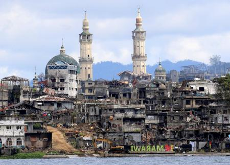 """A signage of """"I love Marawi"""" is seen in front of damaged houses, buildings and a mosque inside a war-torn Marawi city, southern Philippines October 26, 2017, after the Philippines on Monday announced the end of five months of military operations in a southern city held by pro-Islamic State rebels."""