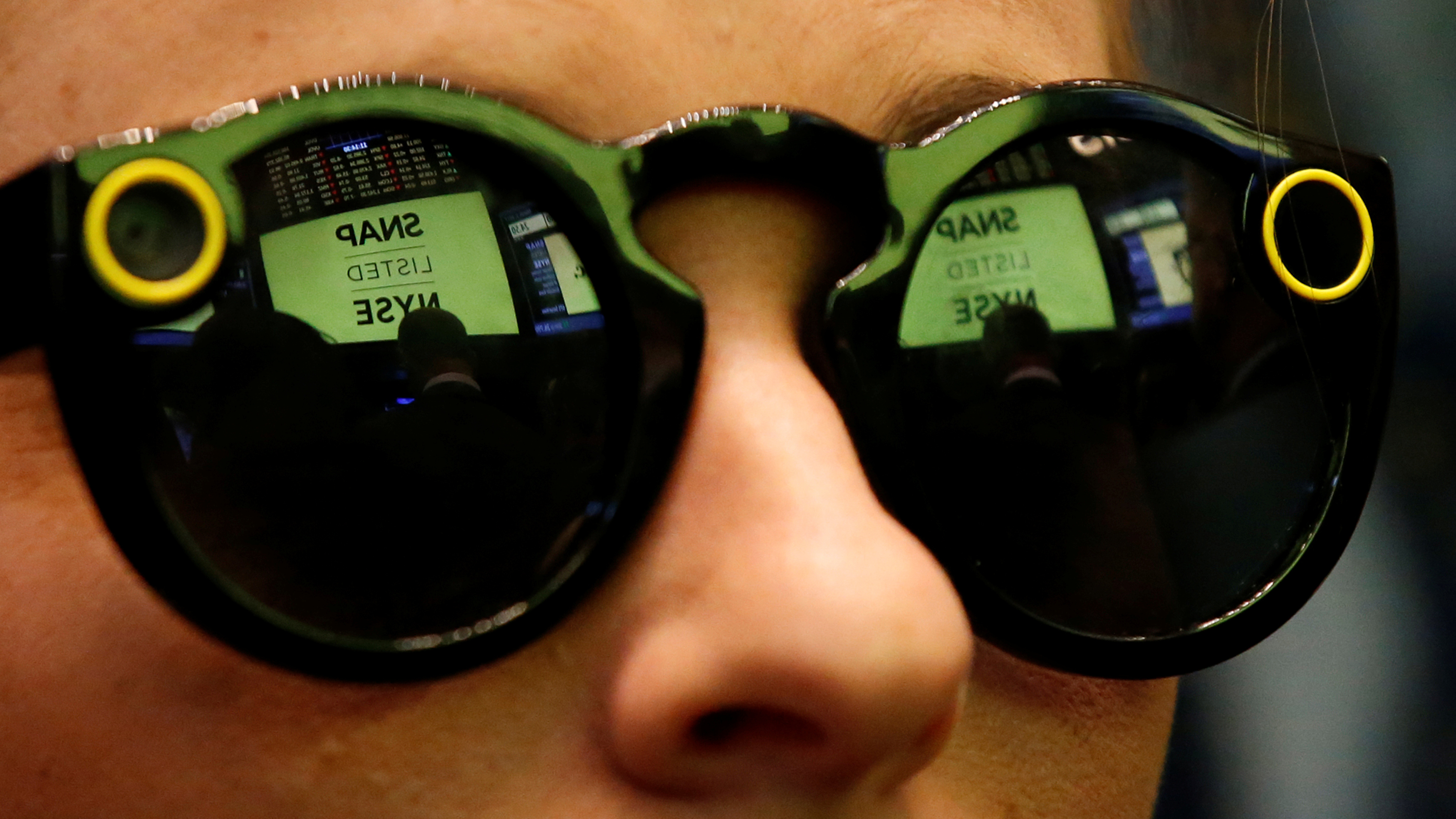 A woman wears Snapchat Spectacles on the floor of the New York Stock Exchange (NYSE) while waiting for Snap Inc. to list their IPO in New York, U.S., March 2, 2017. REUTERS/Brendan McDermid - RC192AA0D180