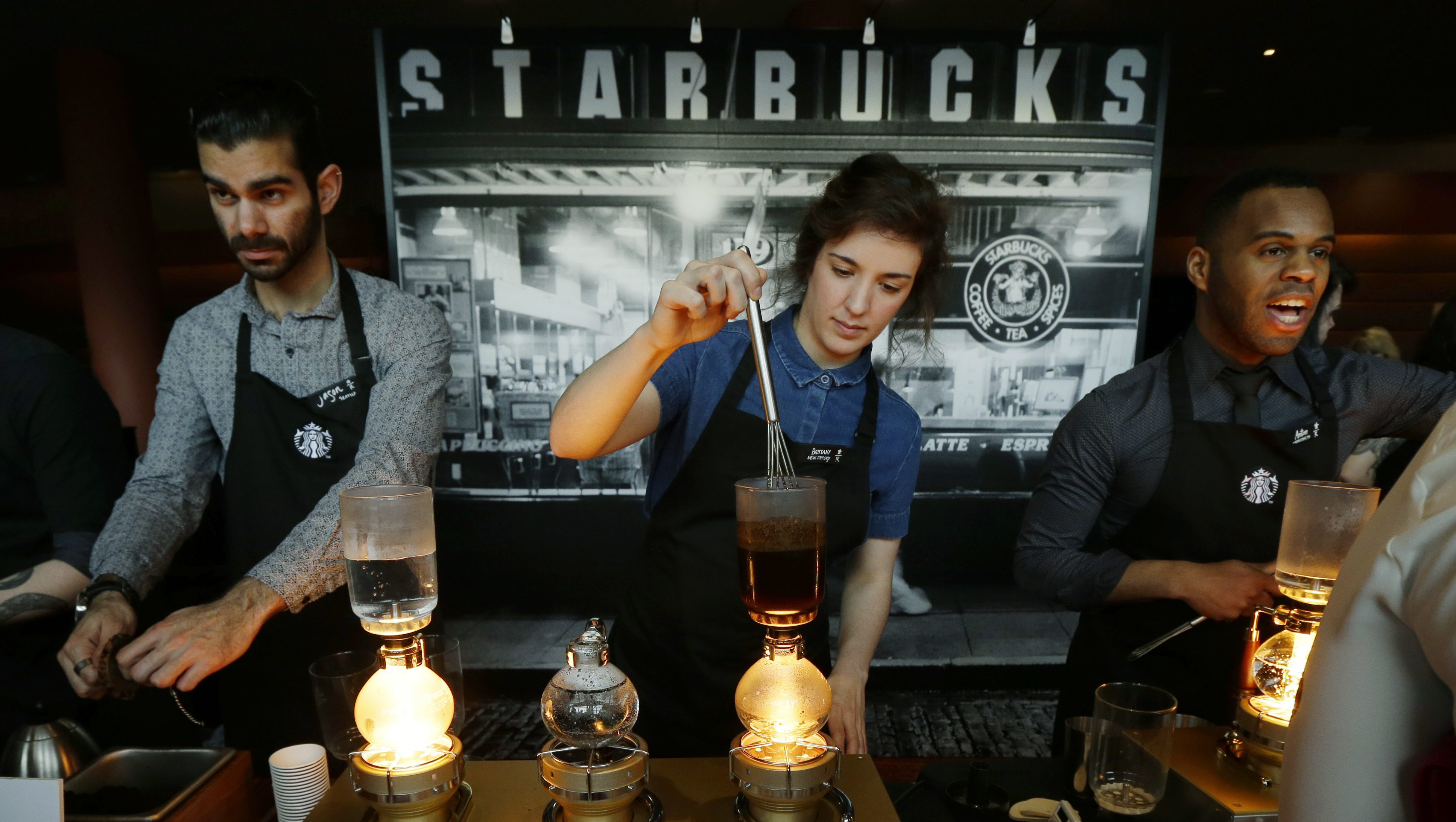 Starbucks workers prepare coffee using siphon vacuum coffee makers at a station in the lobby of the coffee company's annual shareholders meeting in Seattle.