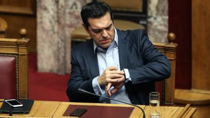 Greece's Prime Minister Alexis Tsipras checks his watch during a parliamentary session in Athens, Saturday, Dec. 10, 2016. Greek parliament votes on 2017 budget, as the country's left-wing government is still negotiating a new series of cost-cutting reforms that are expected to remove protection measures for private sector jobs and distressed mortgage holders. (AP Photo/Yorgos Karahalis)