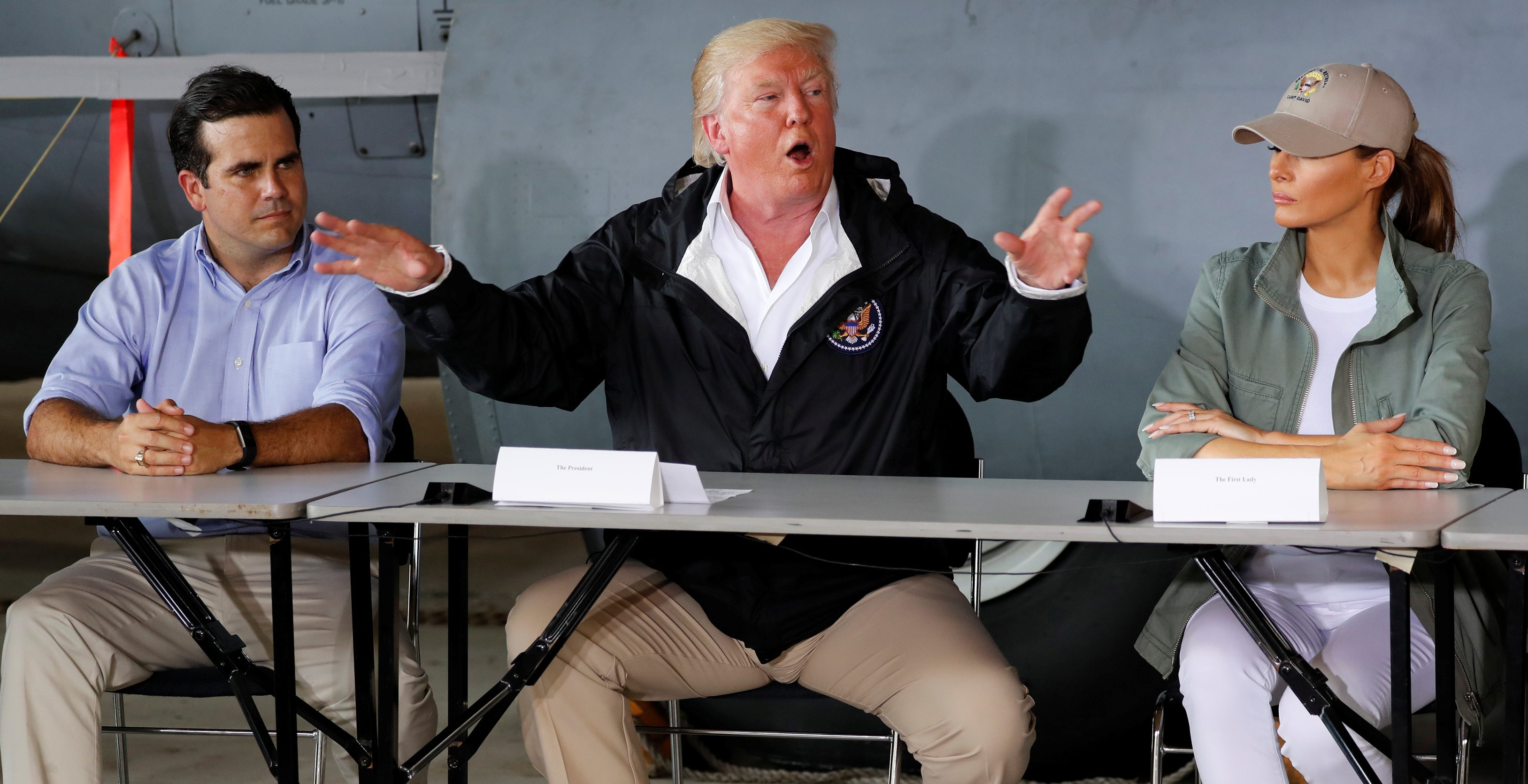 U.S. President Donald Trump, sitting between Puerto Rico Governor Ricardo Rossello and first lady Melania Trump, during his first visit to the island after hurricane Maria