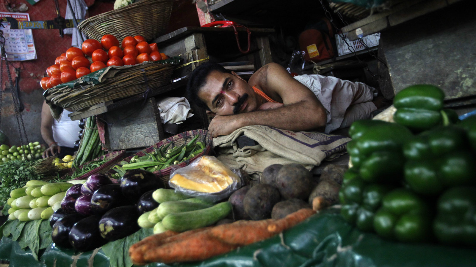 A vegetable vendor in Mumbai rests as he awaits customers.