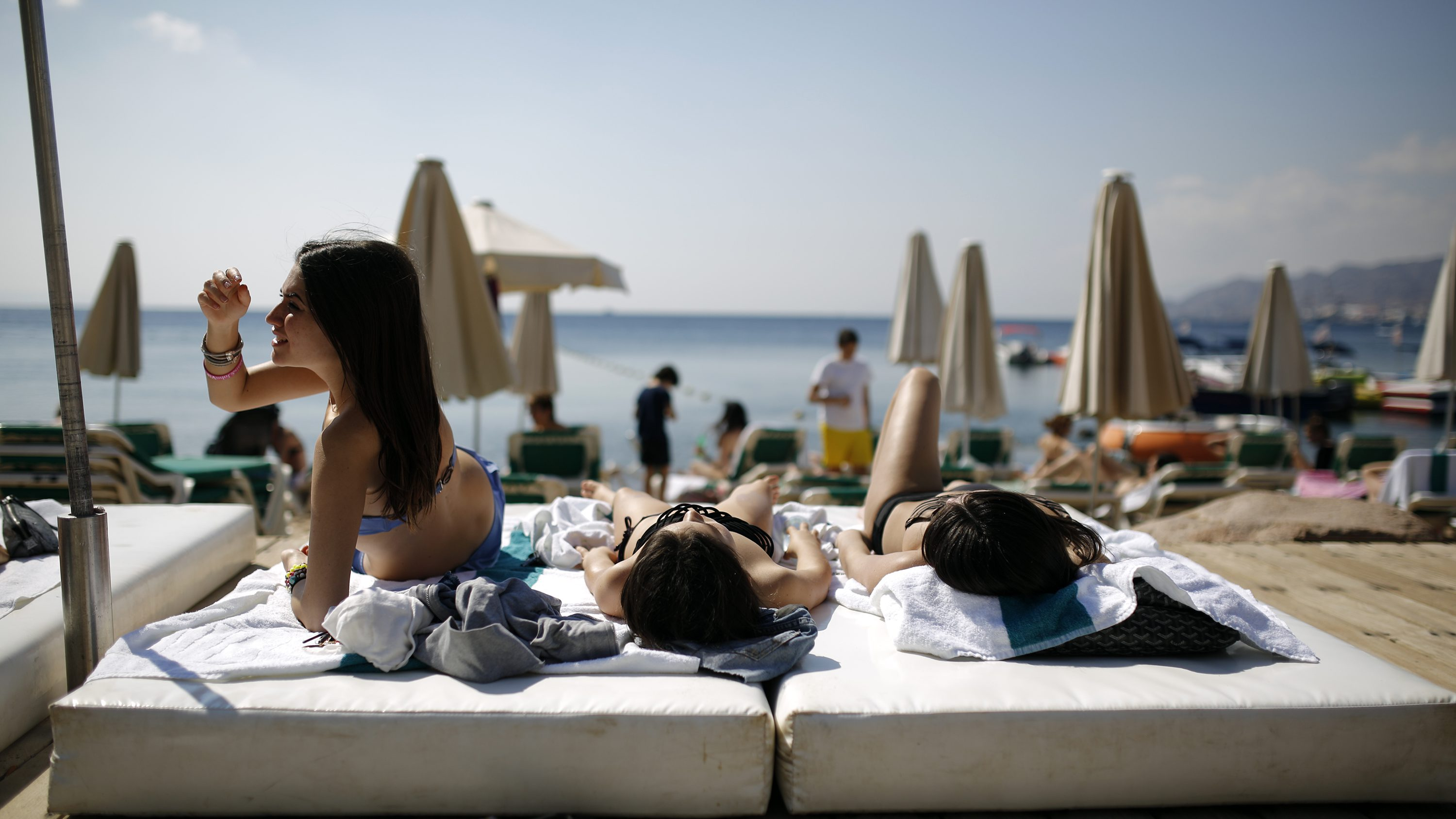 Tourists sunbathe on the beach in the Red Sea resort city of Eilat, one of Israel's most popular holiday spots, February 17, 2014.