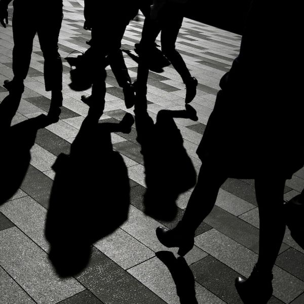 Workers cast shadows as they stroll among the office towers in Sydney's Barangaroo business district