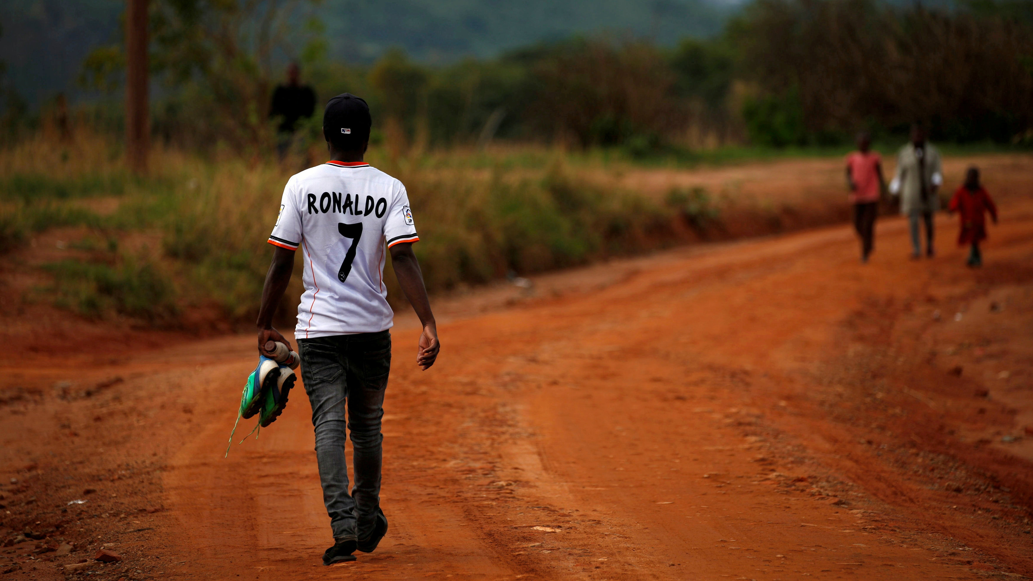 A man wearing a Ronaldo t-shirt and holding soccer shoes walks to take part in a soccer match in Chishawasha village, 27 km east of the capital Harare, Zimbabwe, November 26, 2017.
