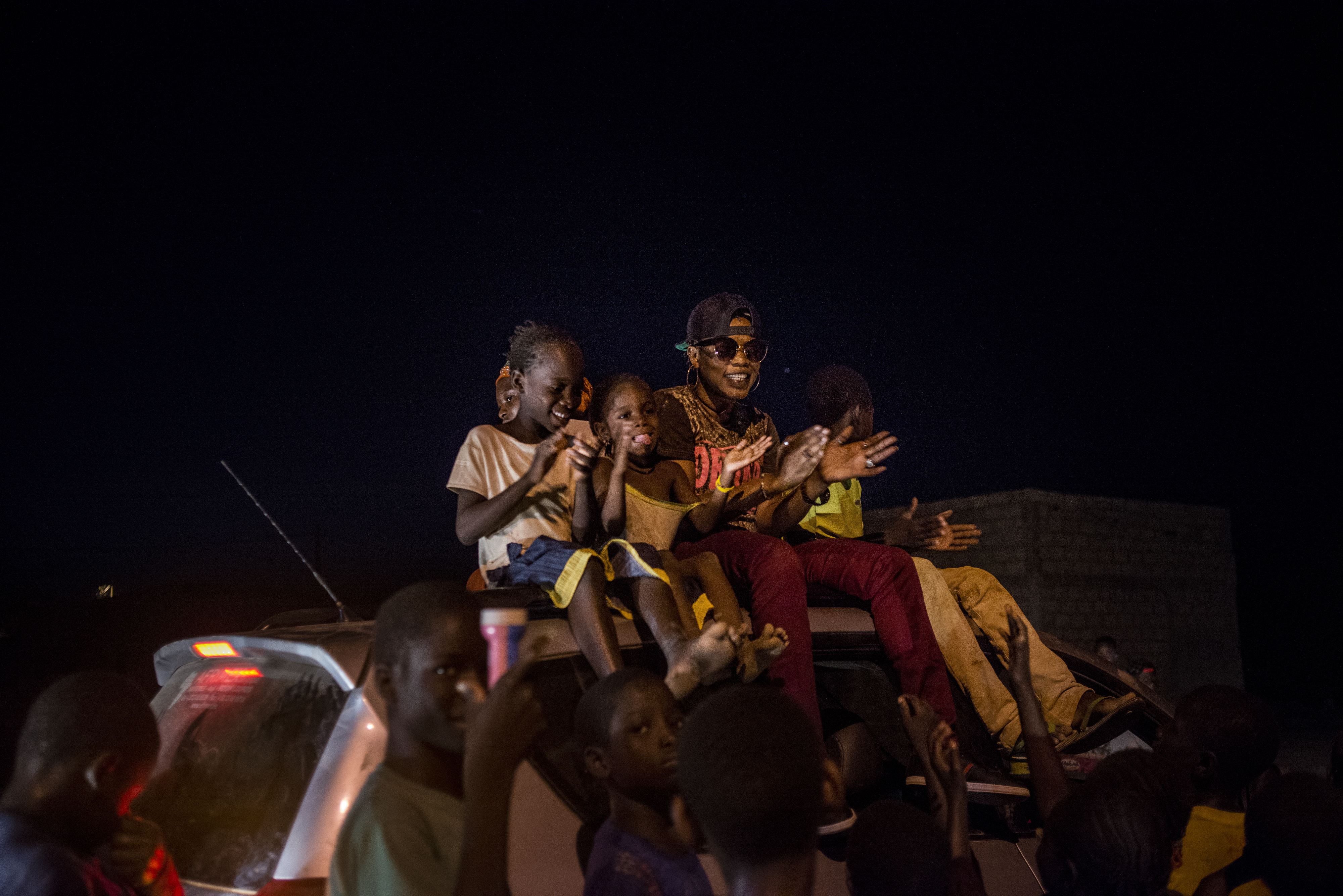 Children from the town join Ami atop a car during her processional around town; young men blasted her music from loudspeakers, announcing her arrival on May 20, 2017 in Macina, Mali.