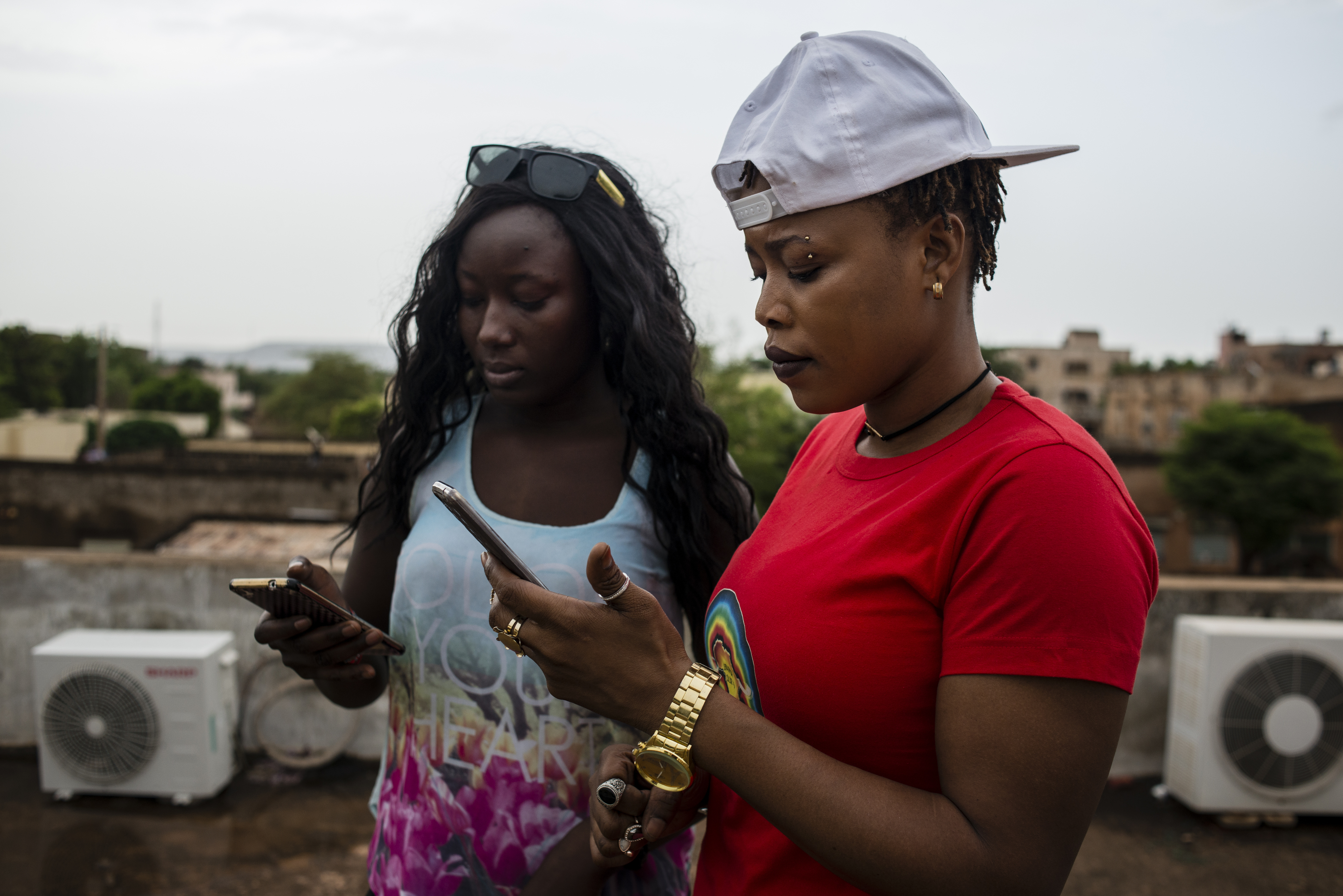 Ami and her friend, also a musician, check their phones after uploading to Instagram on May 22, 2017 in Bamako, Mali.