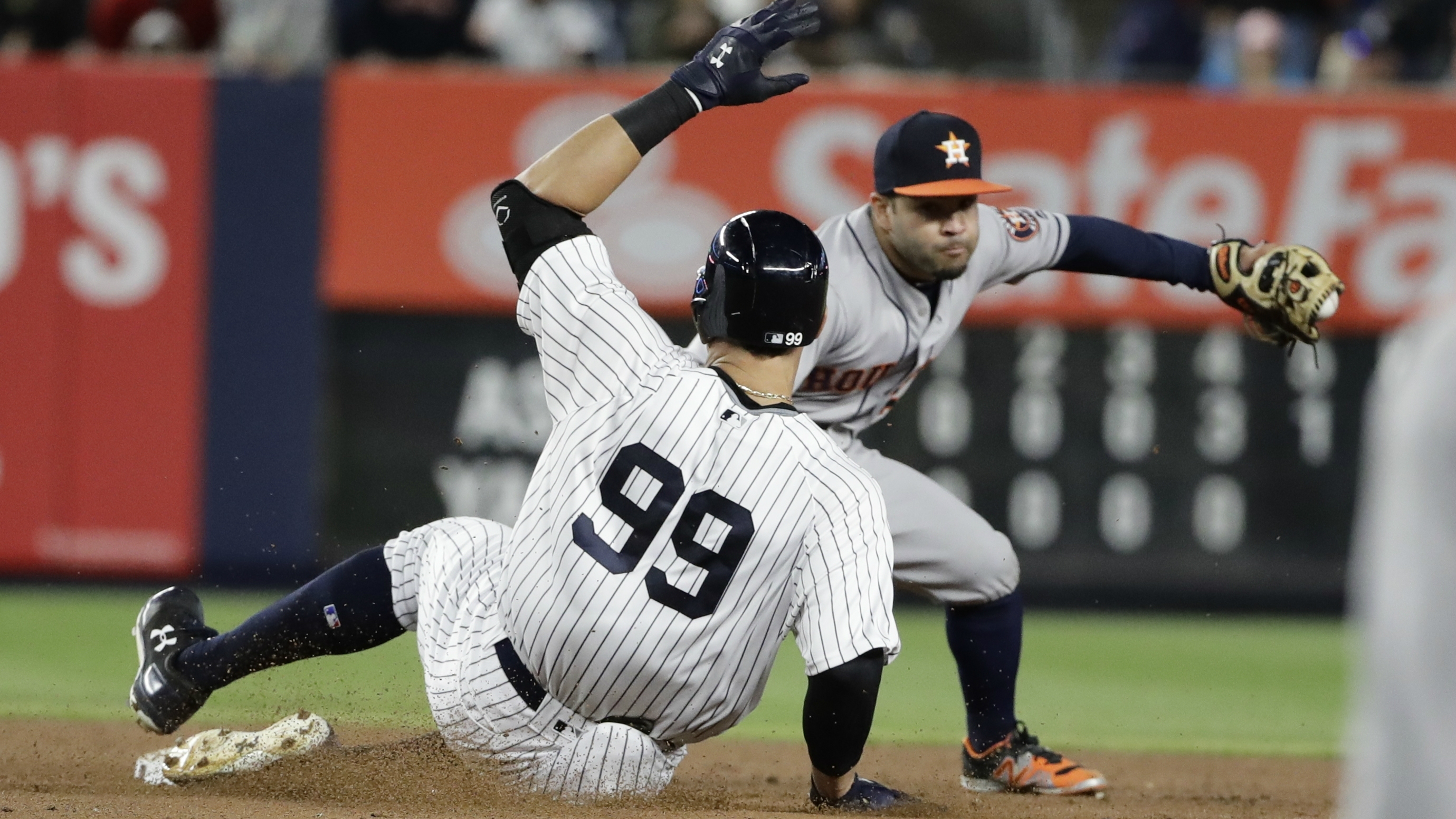 New York Yankees' Aaron Judge (99) slides into second base with a double during the fifth inning as Houston Astros second baseman Jose Altuve waits for the throw in a baseball game.