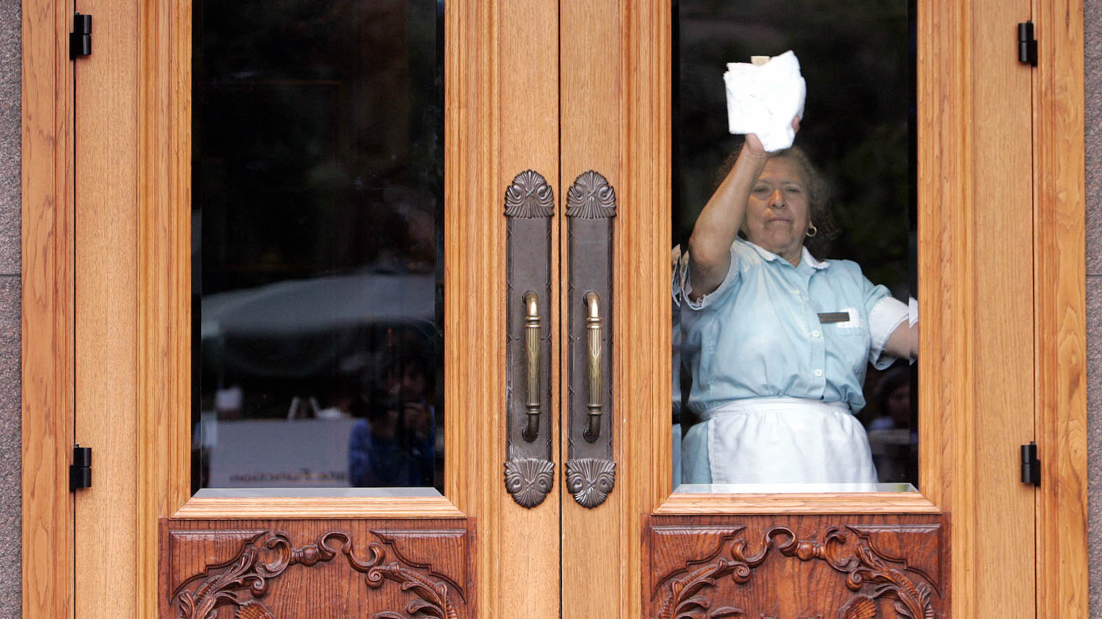 An unidentified maid cleans the windows on doors that participants will enter and exit during the annual Allen & Co. media conference, Wednesday, July 12, 2006, in Sun Valley, Idaho. The conference kicked off last night. (AP Photo/Elaine Thompson)