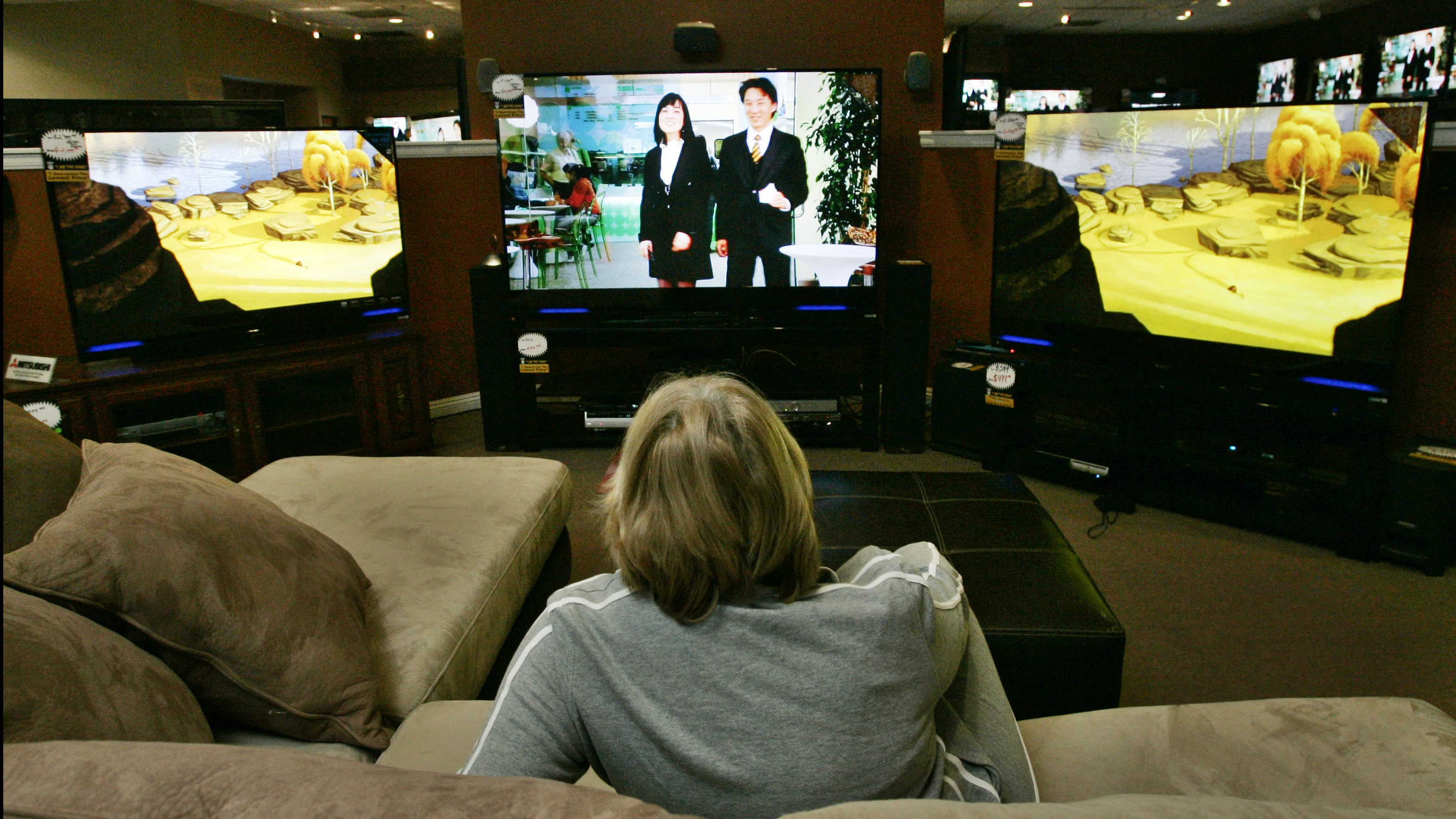 """Mary Addison of Shadow Hills, Calif., checks out televisions and furniture at Paul's """"King of Big Screen"""" TV & Video store in La Habra, Calif., Tuesday, Jan. 29, 2008.  Super Bowl Sunday may be the biggest day of the year for football fans, but it's also a big day for people who sell big screen TVs, recliners and pizza.  (AP Photo/Reed Saxon)"""