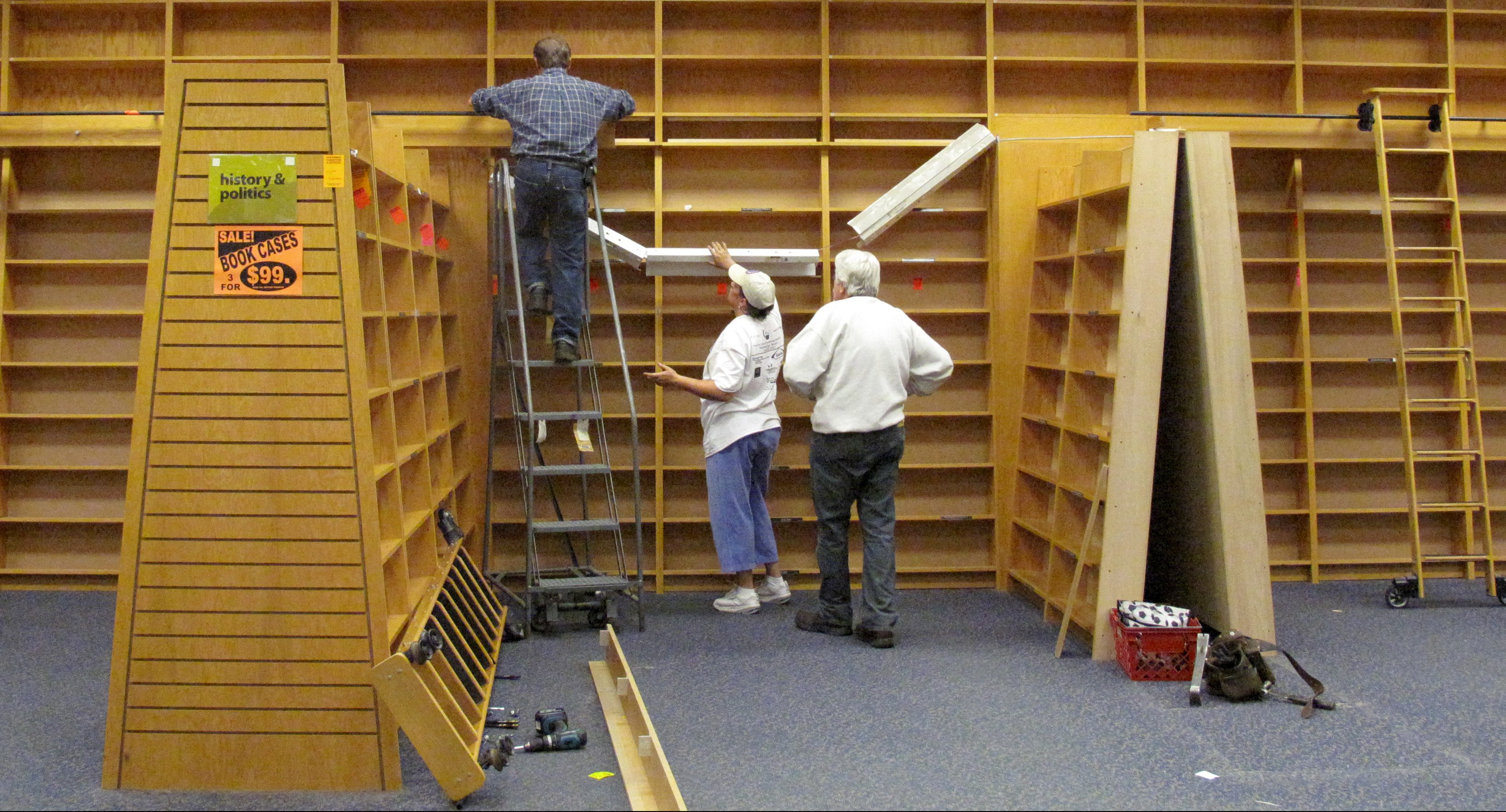 Workers disassemble empty book shelves at the Borders book store in Solon, Ohio on Thursday, Sept. 15, 2022. This Borders store was closing its doors for good on Thursday.  (AP Photo/Amy Sancetta)