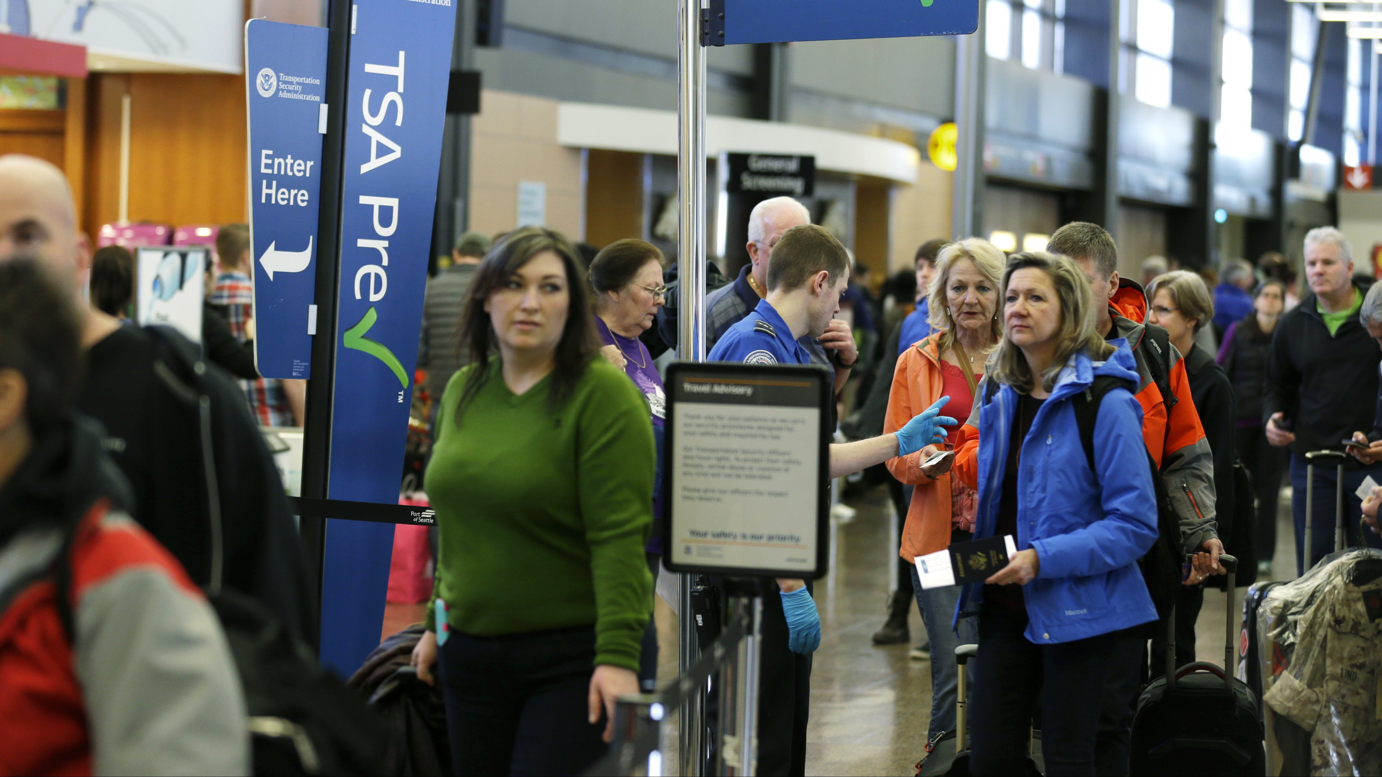 FILE - In this March 17, 2016, file photo, travelers authorized to use the Transportation Security Administration's PreCheck expedited security line at Seattle-Tacoma International Airport in Seattle have their documents checked by TSA workers. Thousands of fliers enrolled in trusted traveler programs such as PreCheck aren't getting the expedited screening they paid for because of clerical errors with their reservations. (AP Photo/Ted S. Warren, File)