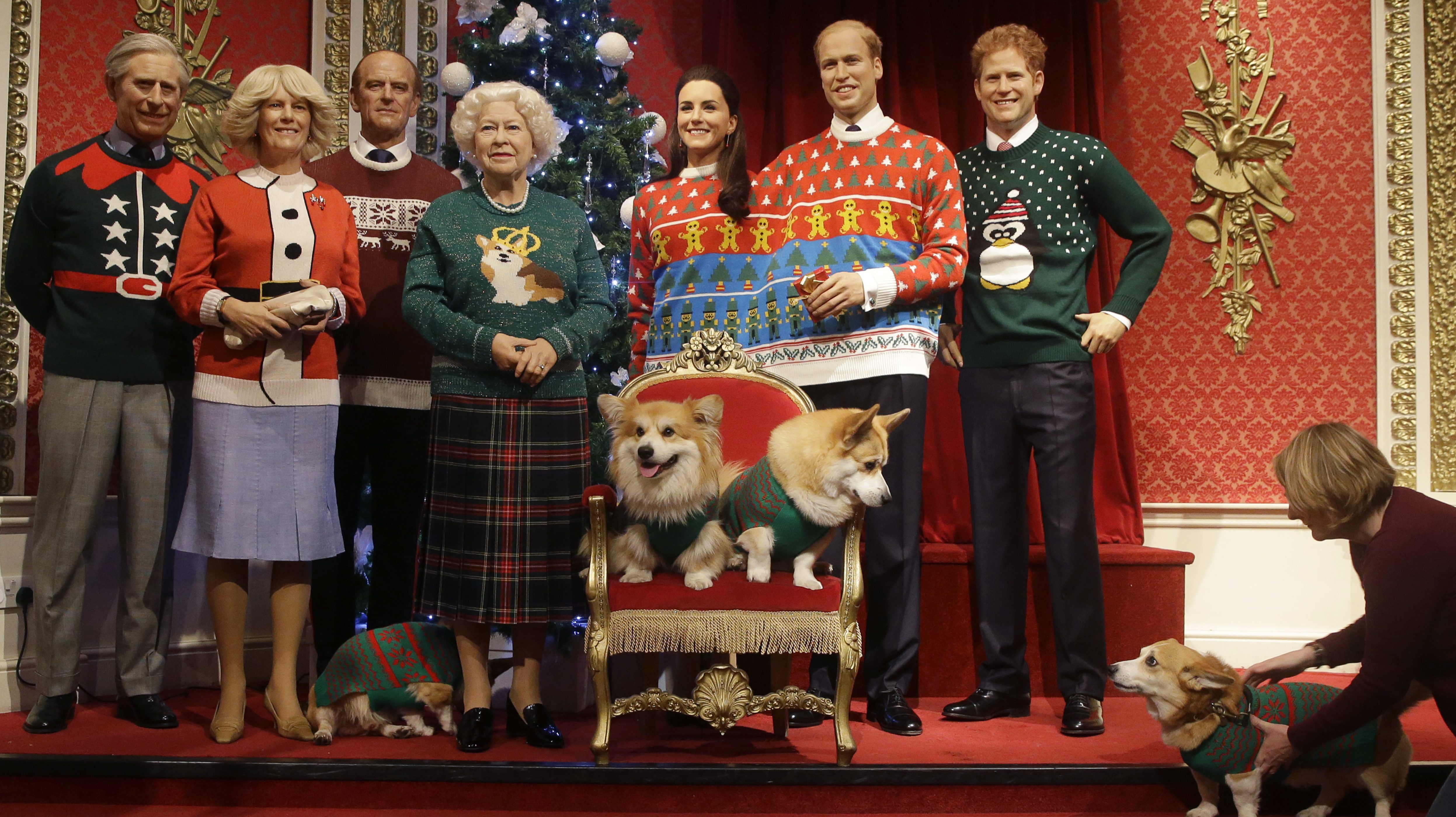Four Corgi dogs pose next to wax work models of the British Royal family wearing colorful Christmas jumpers at Madame Tussauds wax works in London, Tuesday, Dec. 6, 2016.