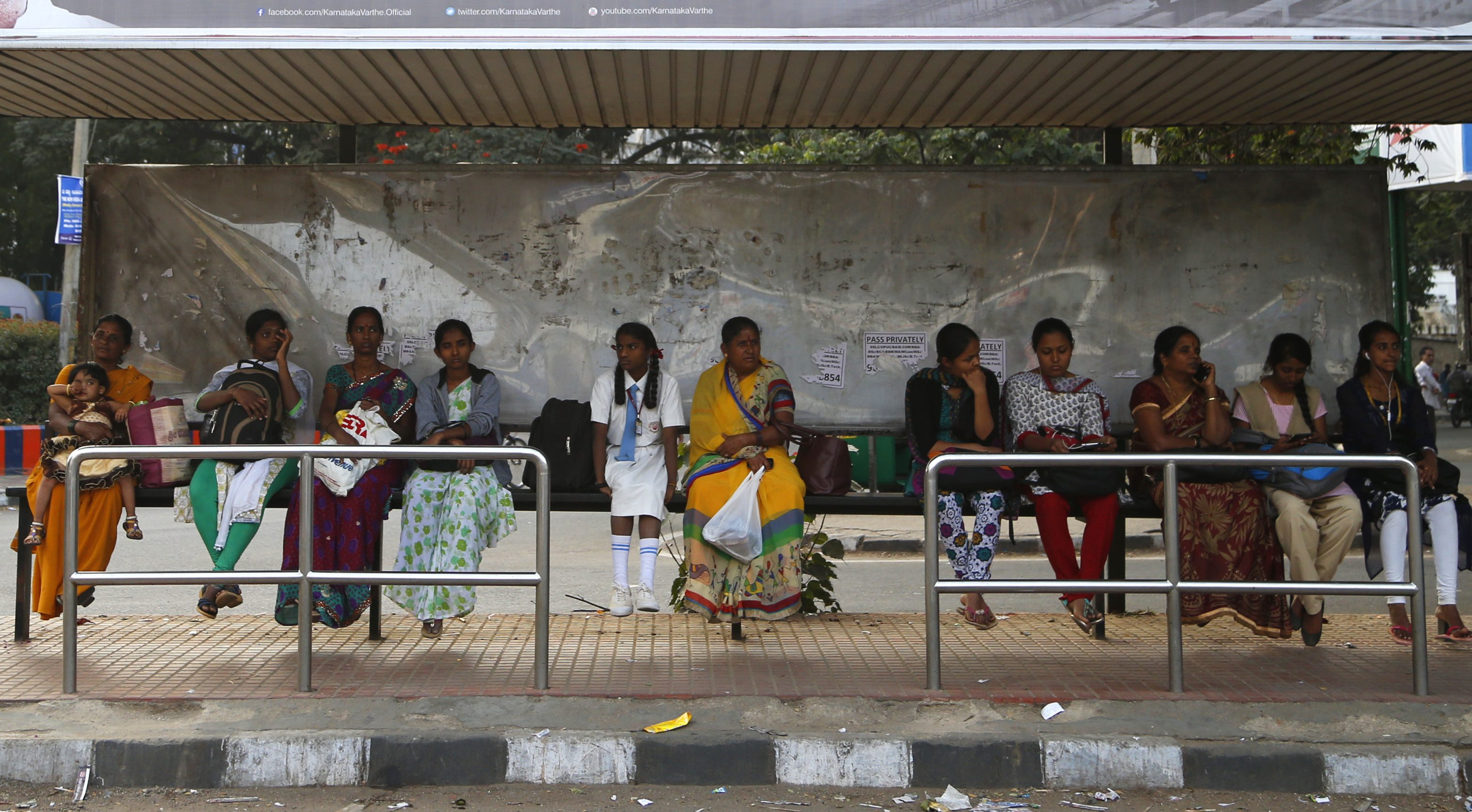 Indian women wait at a bus stop in Bangalore, India, Wednesday, Jan. 4, 2017. Police detained at least six suspects Wednesday, days after outrage erupted in India over several women being groped and molested during New Year's Eve celebrations in the southern city of Bangalore, the country's information technology hub. The incident highlights the persistent violence against women in India despite tougher laws against sexual assault imposed after the December 2012 death of a young woman who was gang-raped on a bus in New Delhi. (AP Photo/Aijaz Rahi)
