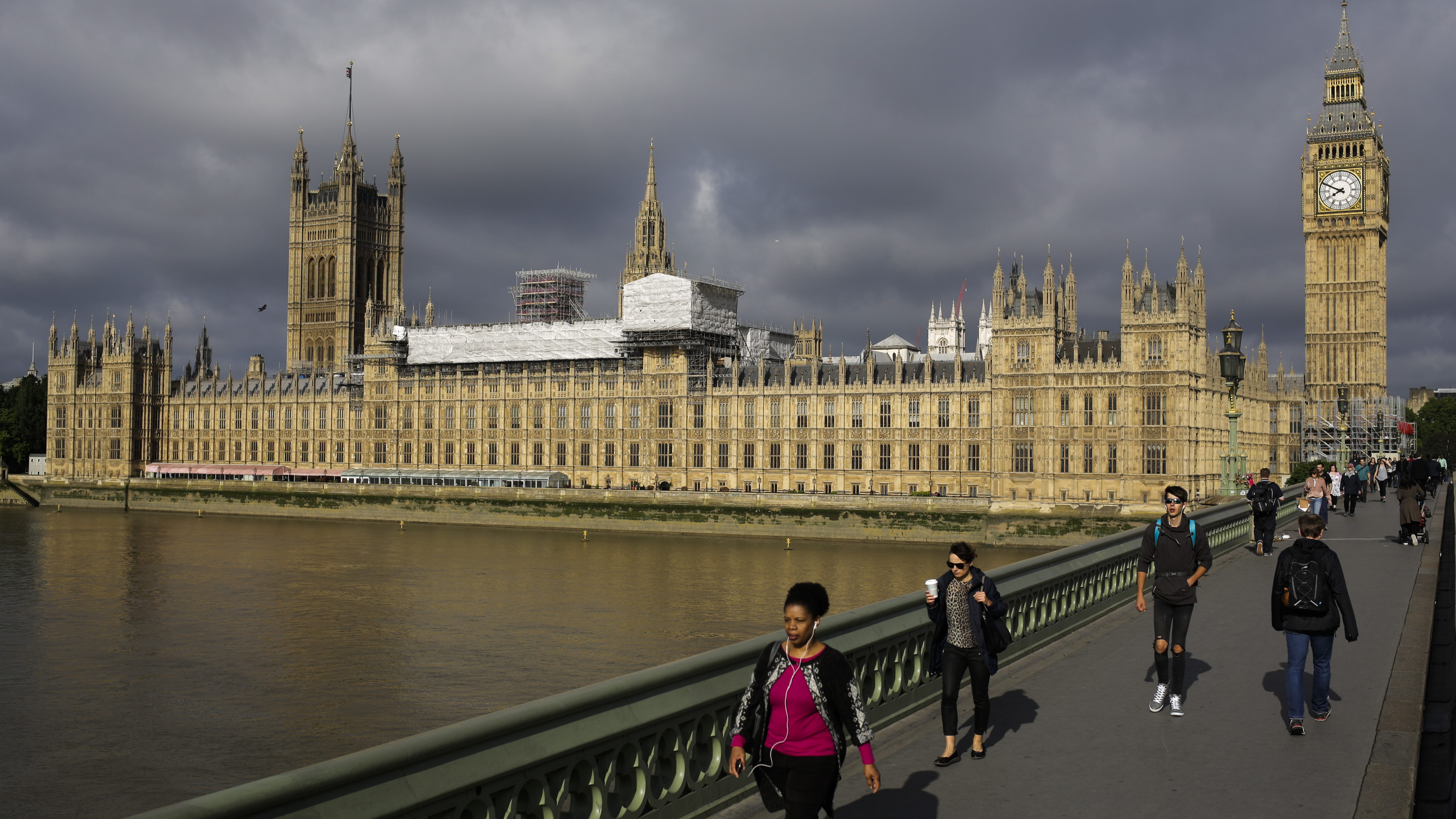 People cross Westminster Bridge in front of the Houses of Parliament the day after Britain's national elections on London, Friday, June 9, 2017. British Prime Minister Theresa May's gamble in calling an early general election backfired spectacularly, as her Conservative Party lost its majority in Parliament and pressure mounted on her Friday to resign. (AP Photo/Markus Schreiber)