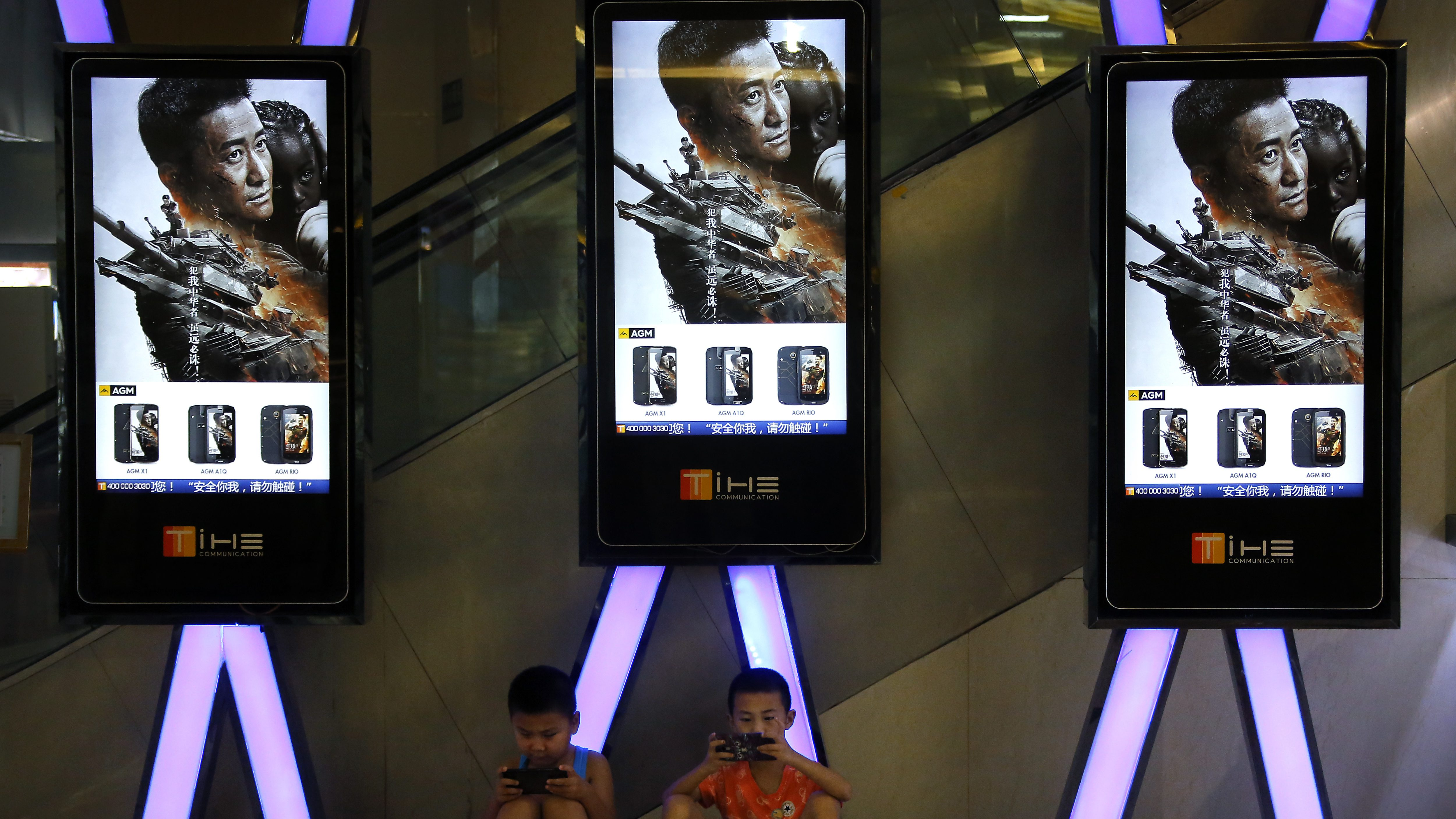 "Children use smartphones near monitors displaying a Chinese action movie ""Wolf Warrior 2"" at a cinema in Beijing, Thursday, Aug. 10, 2017. The A patriotic film reportedly inspired by evacuations of Chinese civilians in Libya and Yemen become China's biggest-ever grossing domestic movie. By Wednesday, action movie ""Wolf Warrior 2"" had raked in more than 3.4 billion yuan ($507 million) since its release on July 27, overtaking Hong Kong director Stephen Chow's 2016 fantasy comedy ""The Mermaid"" in the record books. (AP Photo/Andy Wong)"