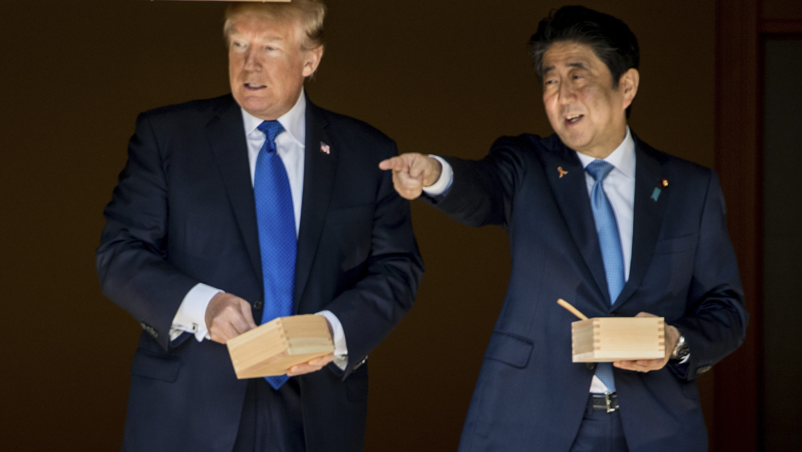 President Donald Trump and Japanese Prime Minister Shinzo Abe speak together while feeding fish at a koi pond at the Akasaka Palace, Monday, Nov. 6, 2017, in Tokyo. Trump is on a five country trip through Asia traveling to Japan, South Korea, China, Vietnam and the Philippines. (AP Photo/Andrew Harnik)