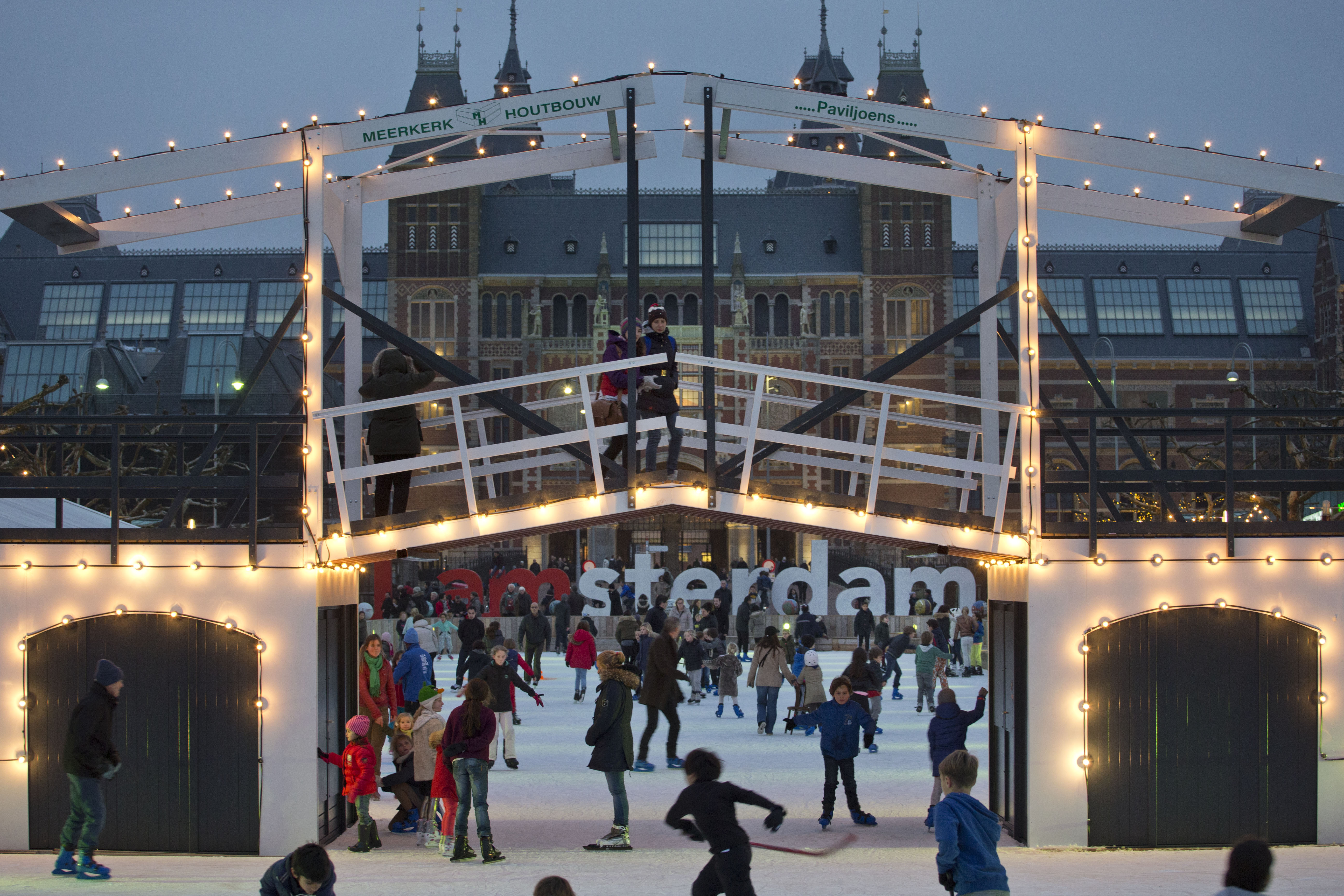 Skaters pass under a decorative draw bridge constructed over a pond that serves as an once rink in the winter months outside the newly renovated Rijksmuseum, rear, in Amsterdam, Netherlands, Tuesday, Dec. 3, 2013. (AP Photo/Peter Dejong)