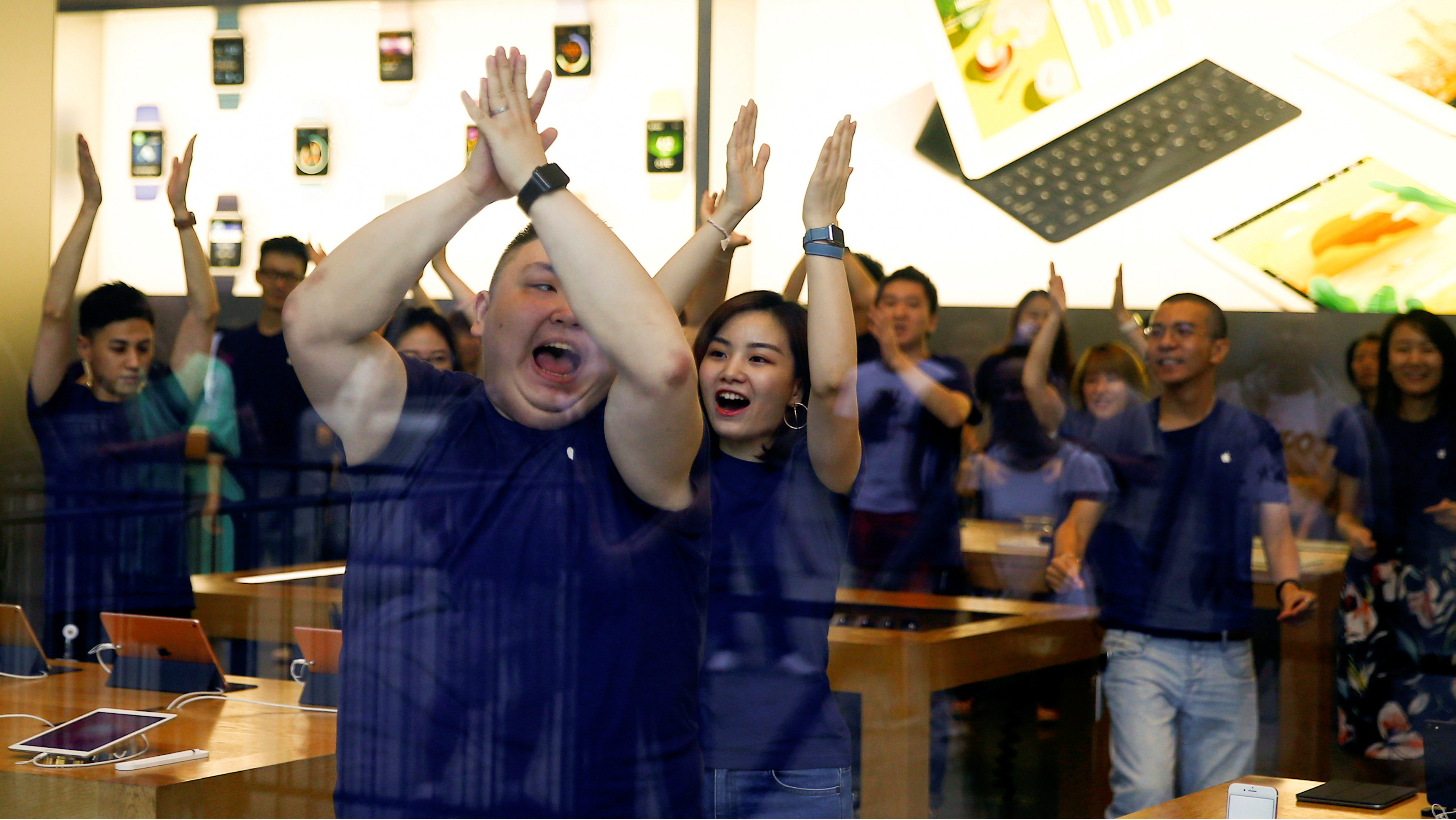Staff members perform a dance routine before opening an Apple store to customers who line up to purchase the new iPhone 7 in Beijing, China, September 16, 2016.