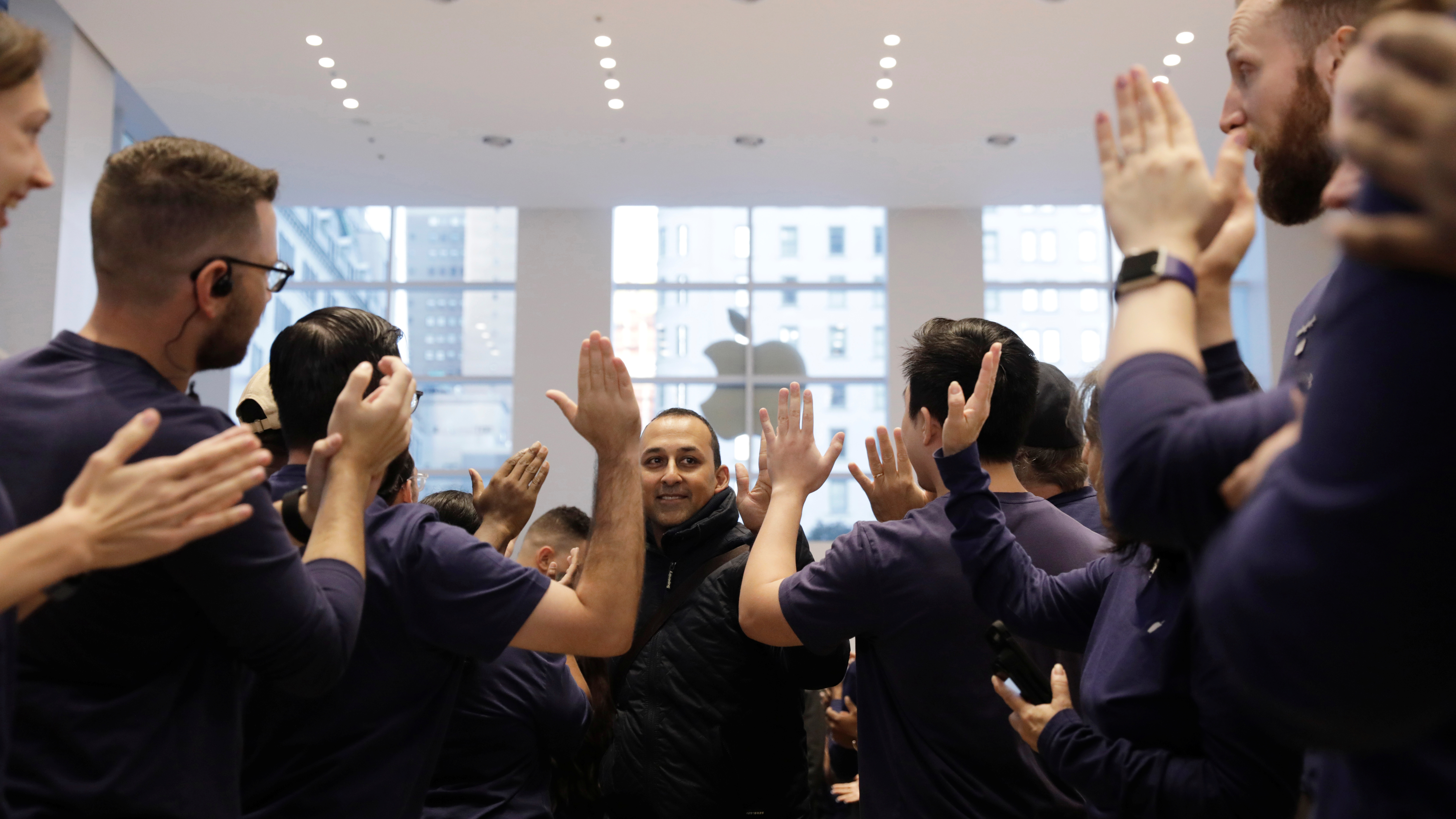 A customer is greeted by Apple employees as he enters an Apple store to purchase an iPhone X in New York, U.S., November 3, 2017.  REUTERS/Lucas Jackson - RC1CB0BE5FD0