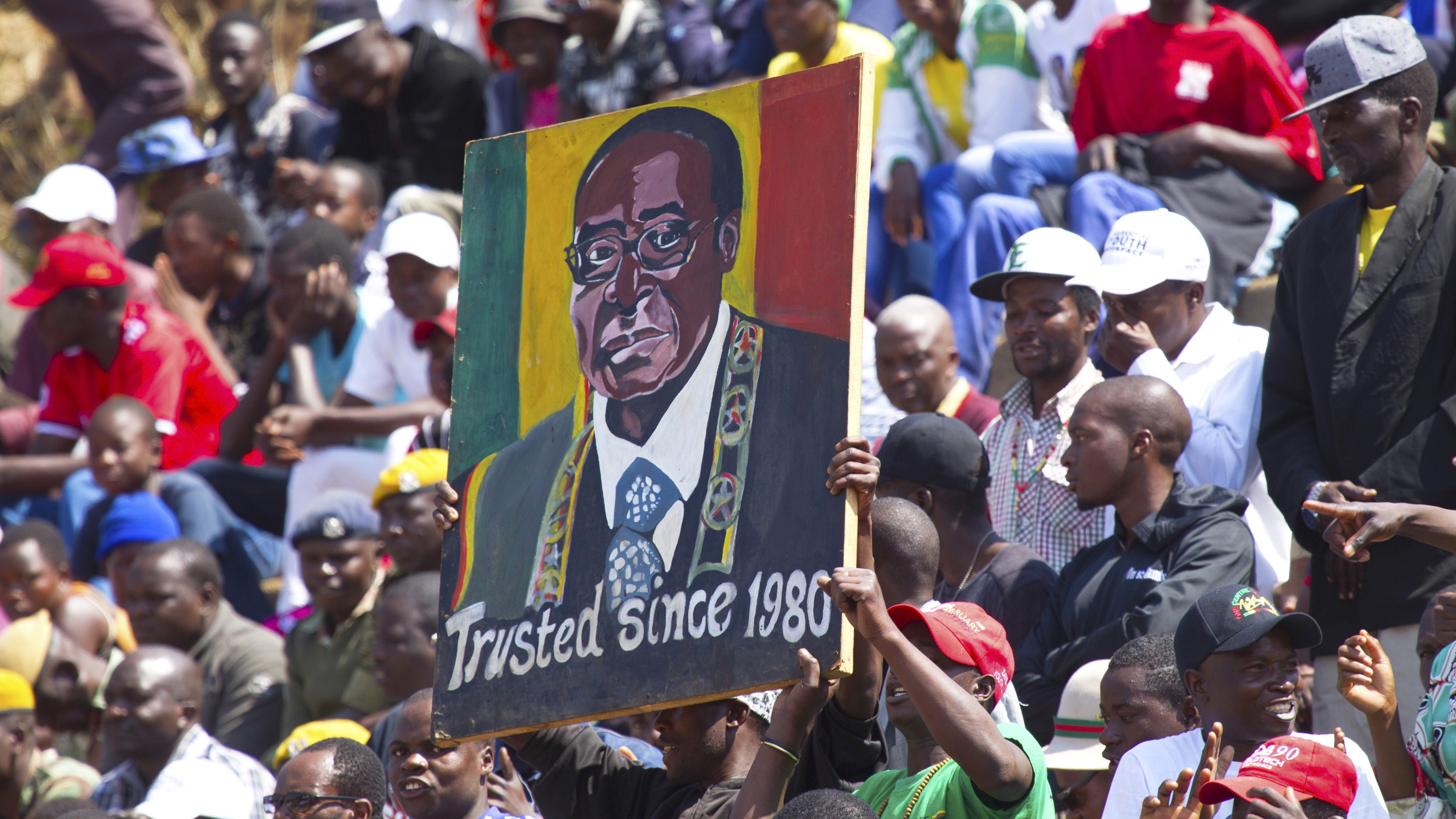 Supporters of Zimbabwean President Robert Mugabe  carry his portrait at a state funeral in Harare, Sunday. August, 20, 2017. Mugabe  and his wife Grace did not attend the  funeral  following  their return  from Johannesburg, where the First lady  faced calls for  prosecution for allegedly assaulting a woman.The Mugabe couple returned early Sunday, from South Africa where the President was  attending a summitt  for Southern African countries(AP Photo/Tsvangirayi Mukwazhi)