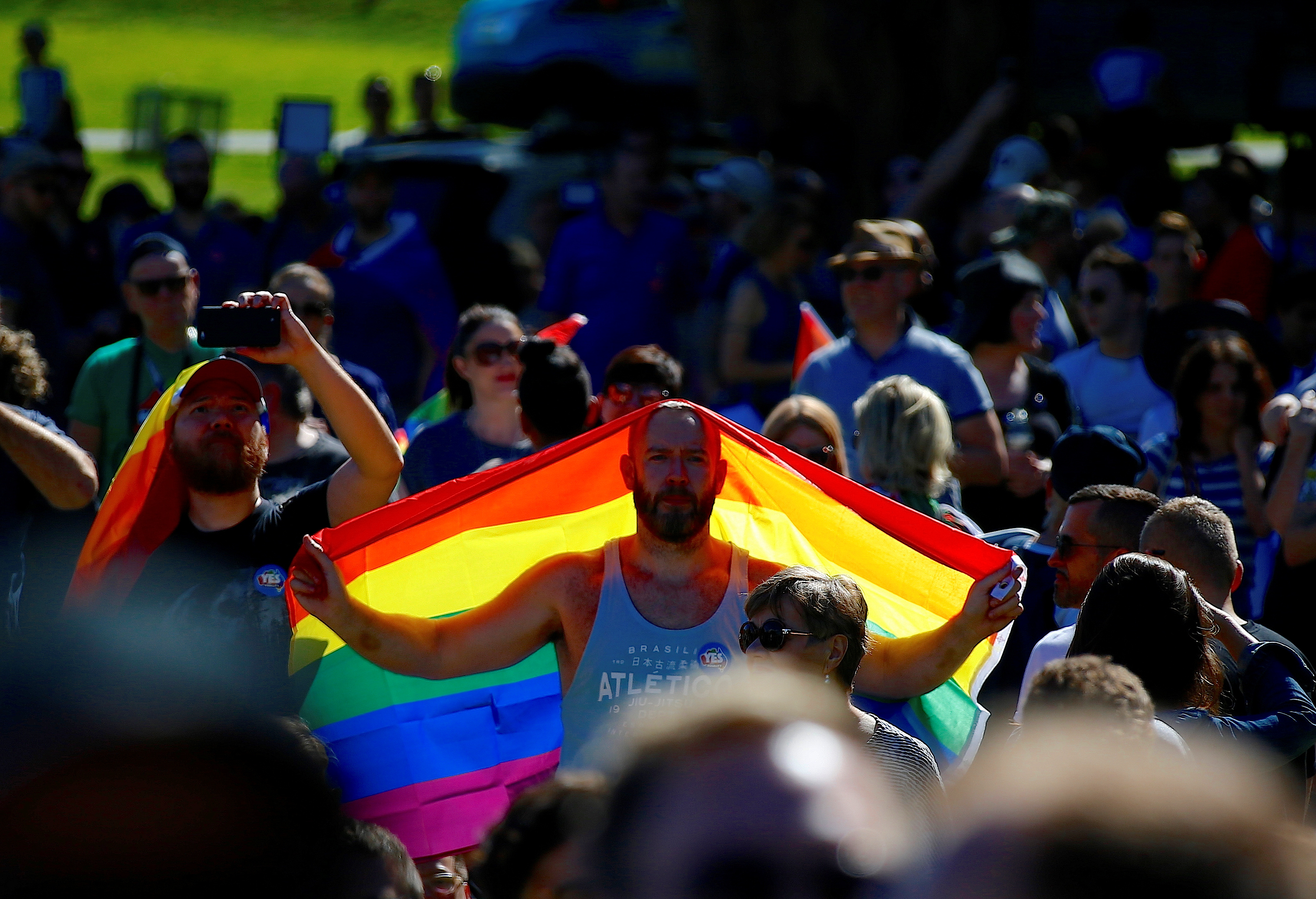 A supporter of the 'Yes' vote holds a colourful flag as he celebrates after it was announced the majority of Australians support same-sex marriage in a national survey, paving the way for legislation to make the country the 26th nation to formalise the unions by the end of the year, at a rally in central Sydney, Australia, November 15, 2017.  REUTERS/David Gray - RC1B4D37EB00