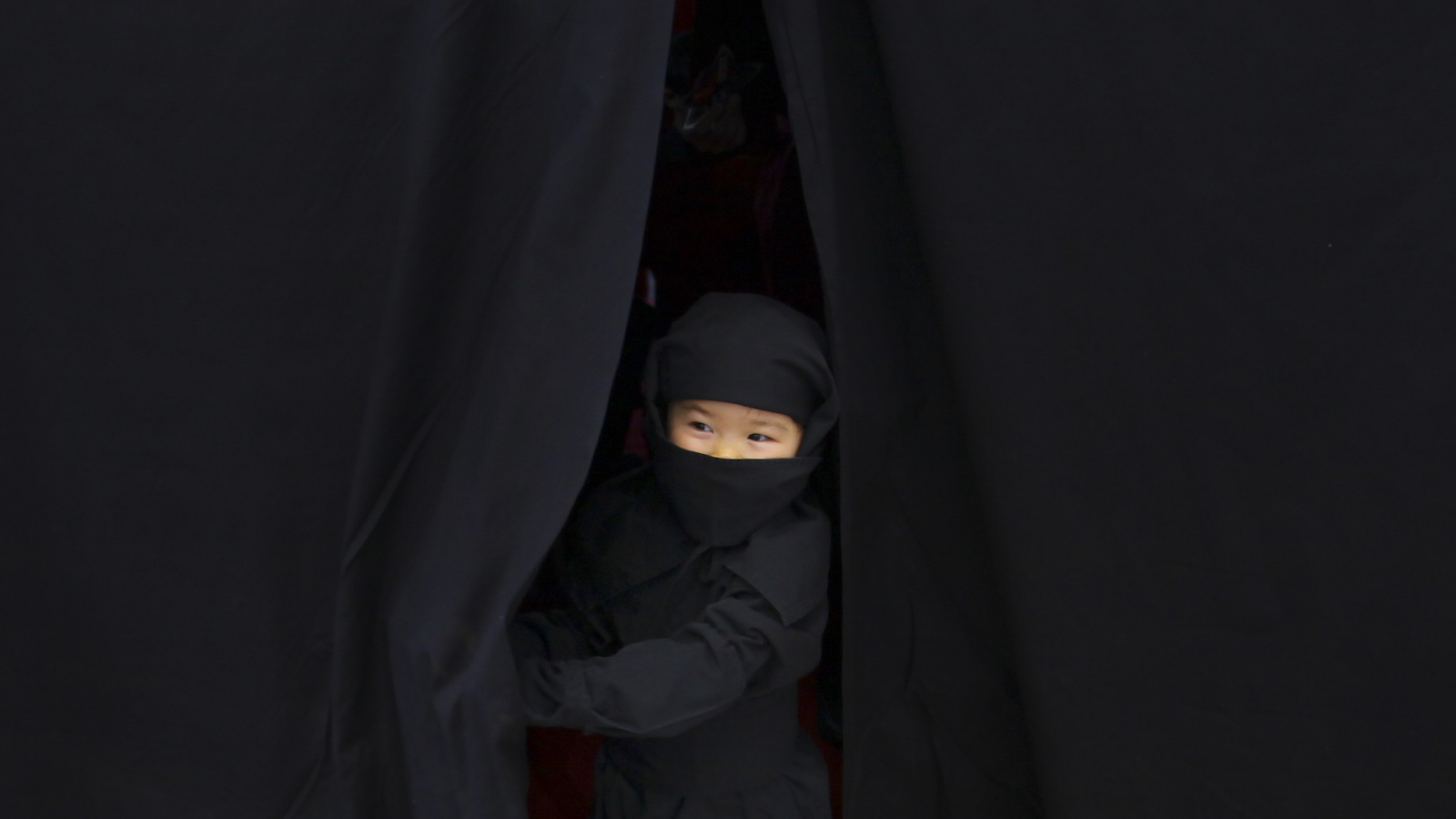Shizuku Morita of Tokyo, 3, comes out of a dressing room with Ninja outfit at a mall during a Japan Week event in Tokyo Saturday, Feb. 5, 2011 to promote Japan's culture including tourism to Iga city, one of the places where Ninja was originated. (AP Photo/Junji Kurokawa)