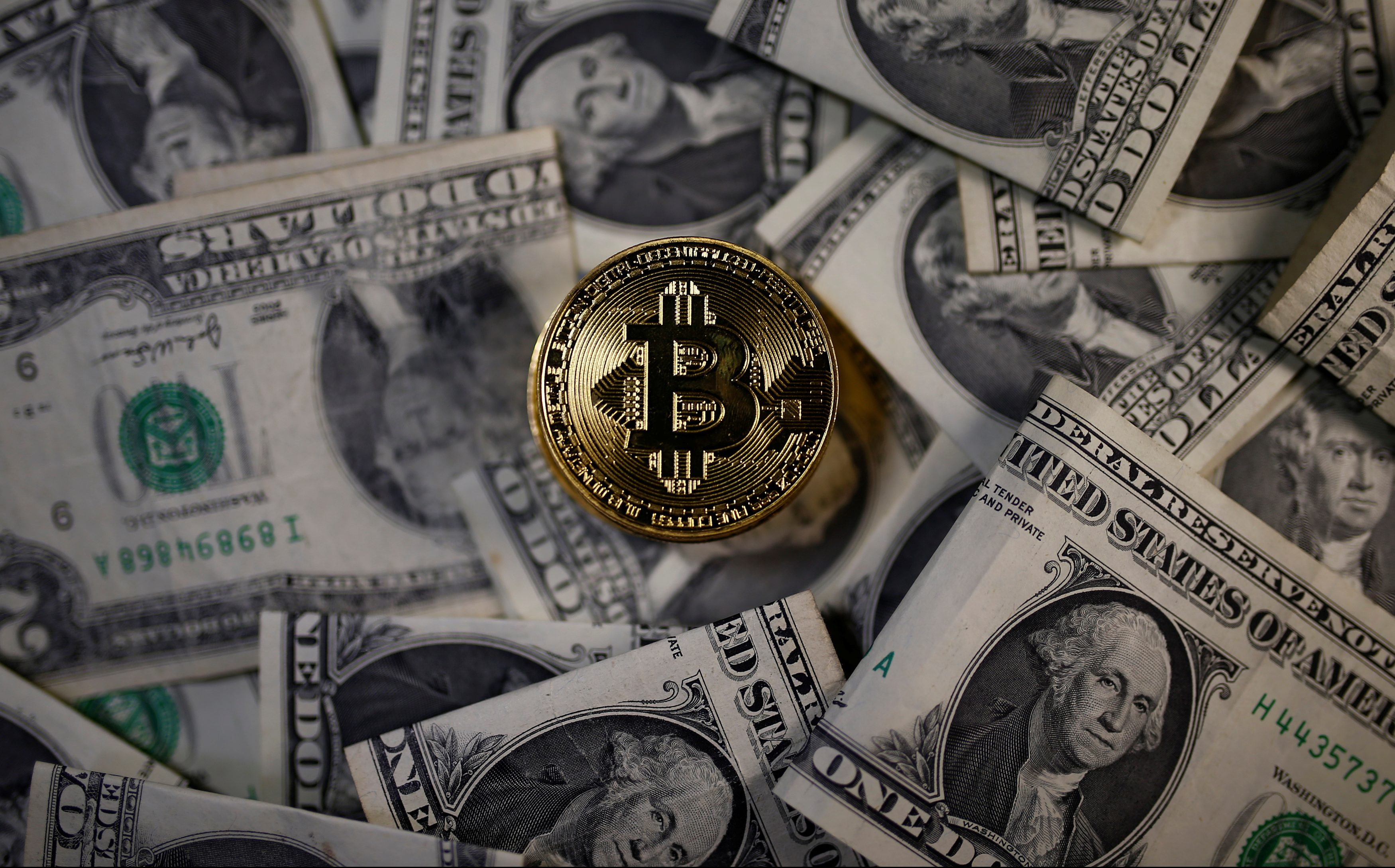 A bitcoin (virtual currency) coin placed on Dollar banknotes is seen in this illustration picture, November 6, 2017.