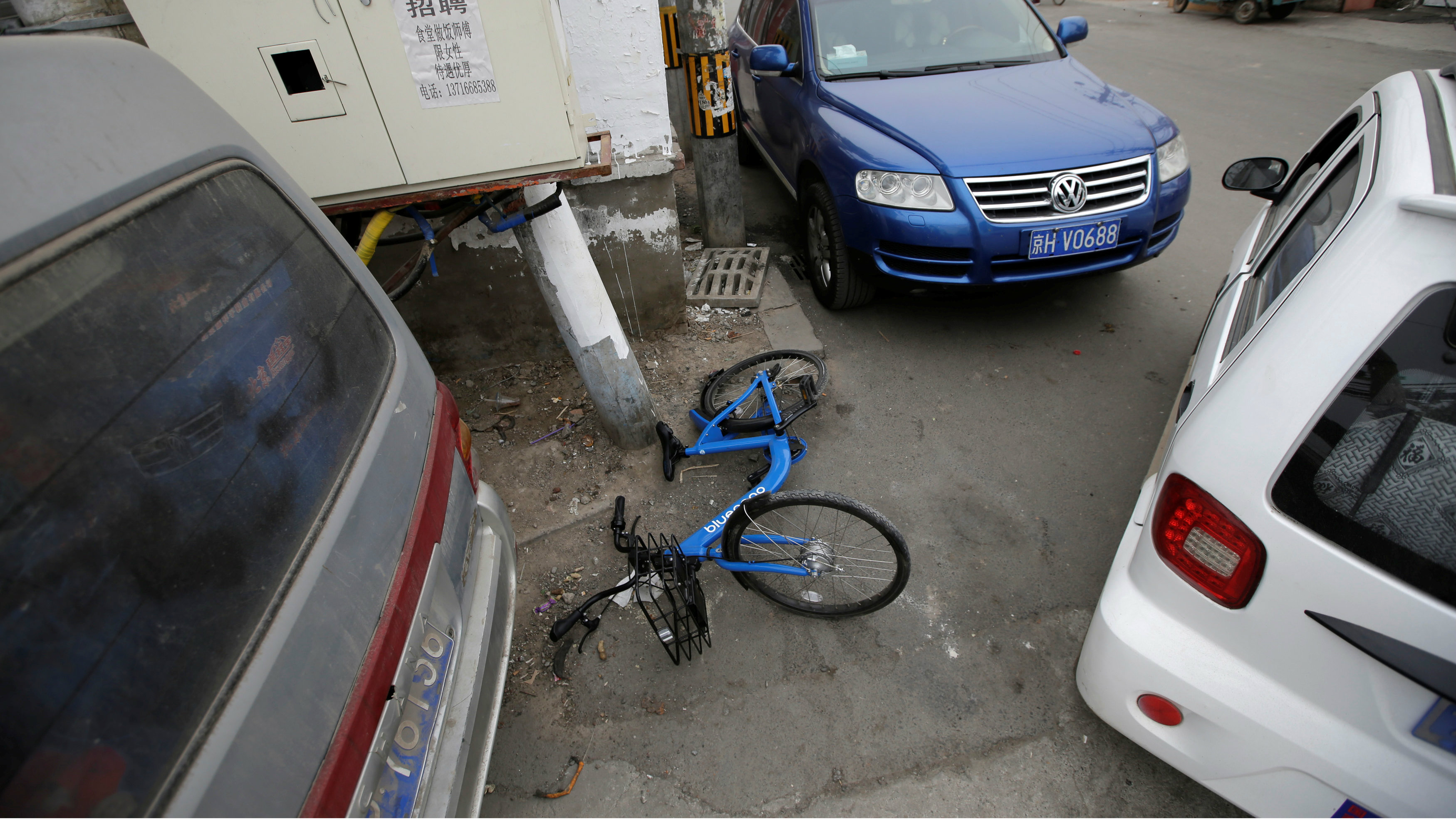 A Bluegogo's shared bike lies among vehicles at a residential area for migrant workers in a village on the outskirts of Beijing, China