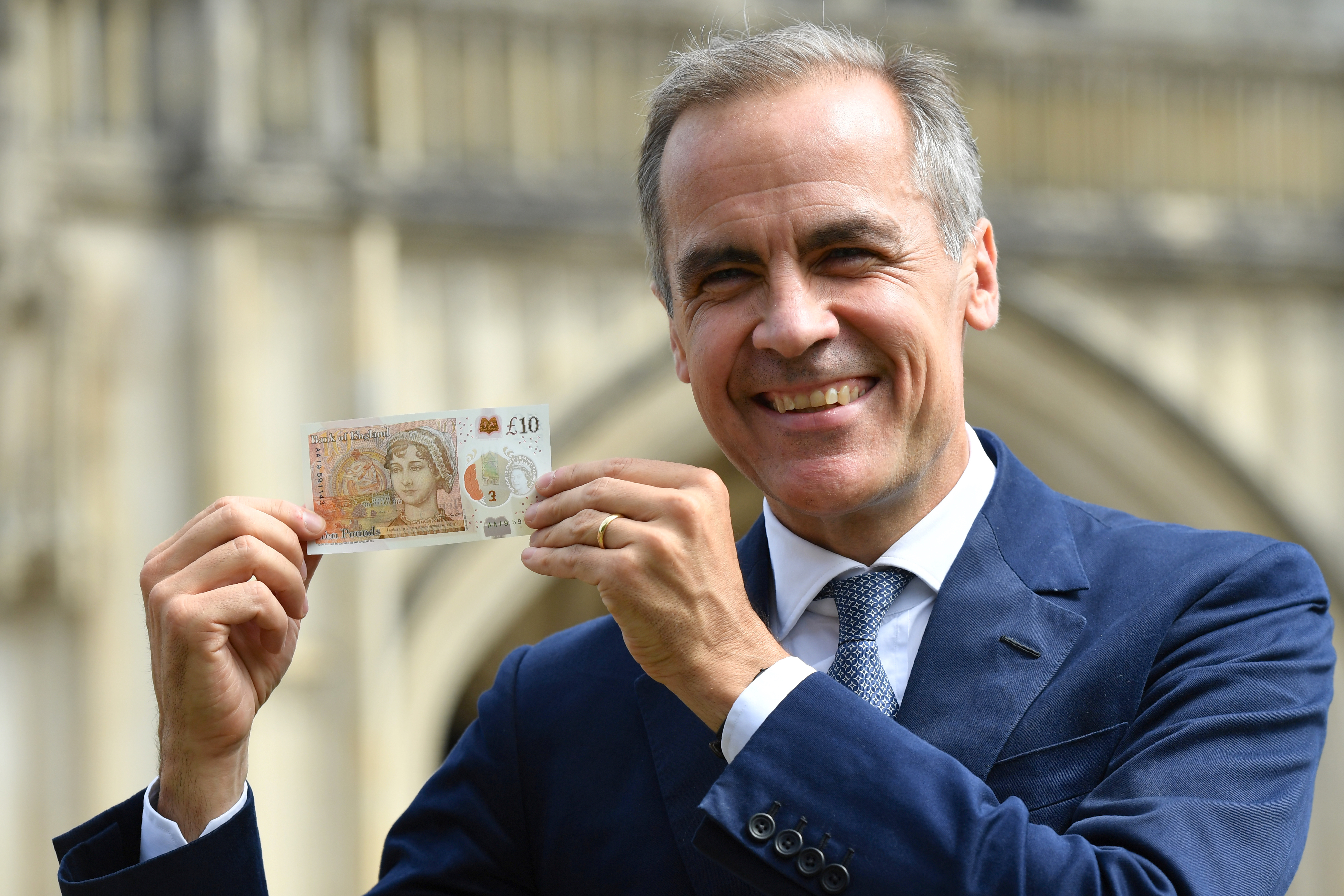 Mark Carney of the Bank of England holds up a banknote
