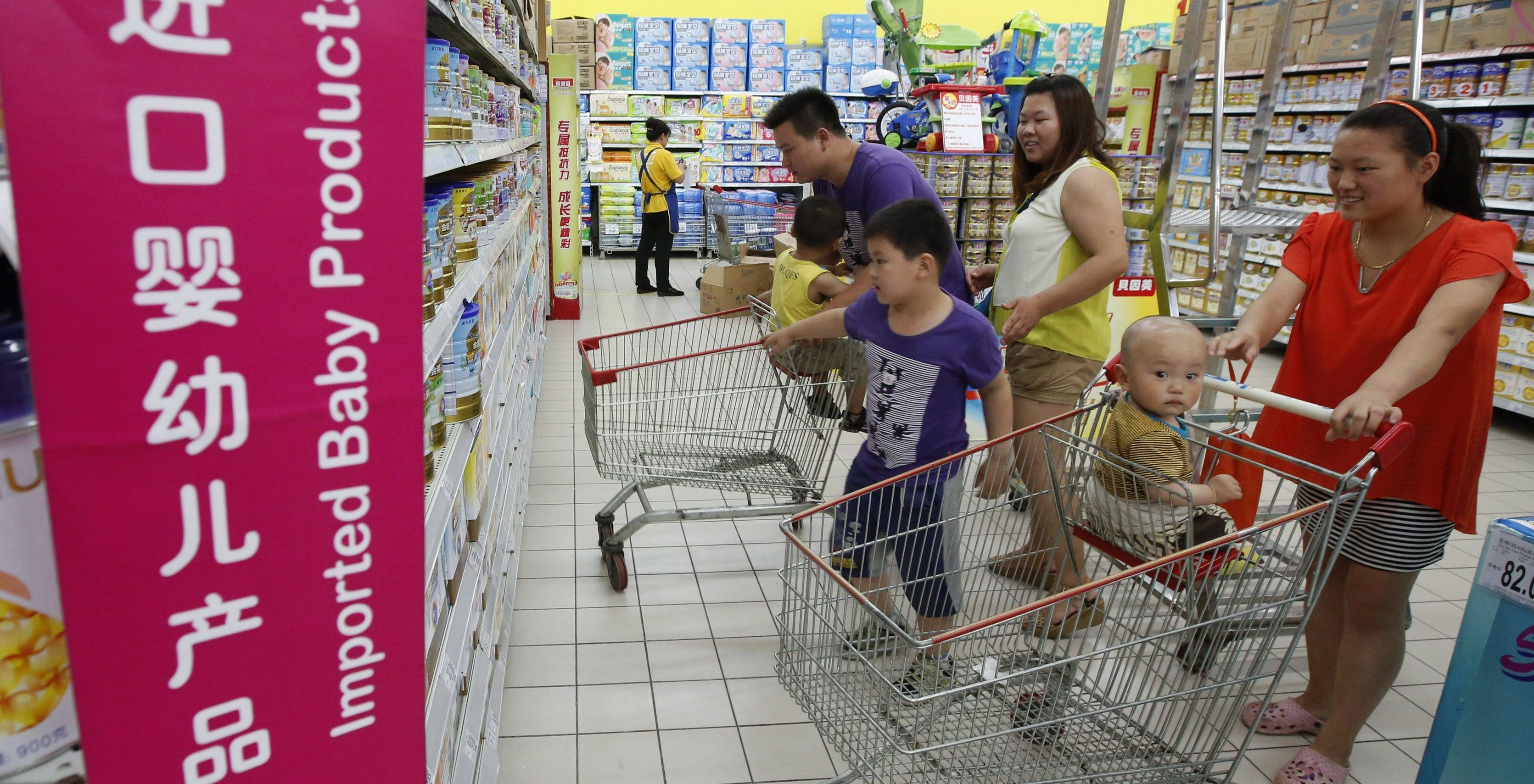 A family looks at foreign imported milk powder products at a supermarket in Beijing July 3, 2013. The decision by China's top economic planner to investigate five leading foreign infant milk companies for suspected antitrust violations may be part of a broader plan to boost consumption of the local product, analysts said on Wednesday. Mothers turned away from Chinese milk powder in 2008 when infant formula tainted with the industrial compound melamine killed at least six babies and made thousands sick with kidney stones.