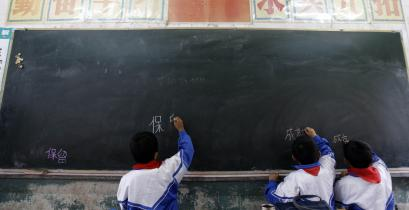 Pupils write Chinese characters on the blackboard during a class at an elementary school in the rural village of Gongshan on the bank of the Nu River, in southwest China's Yunnan province March 2, 2007.