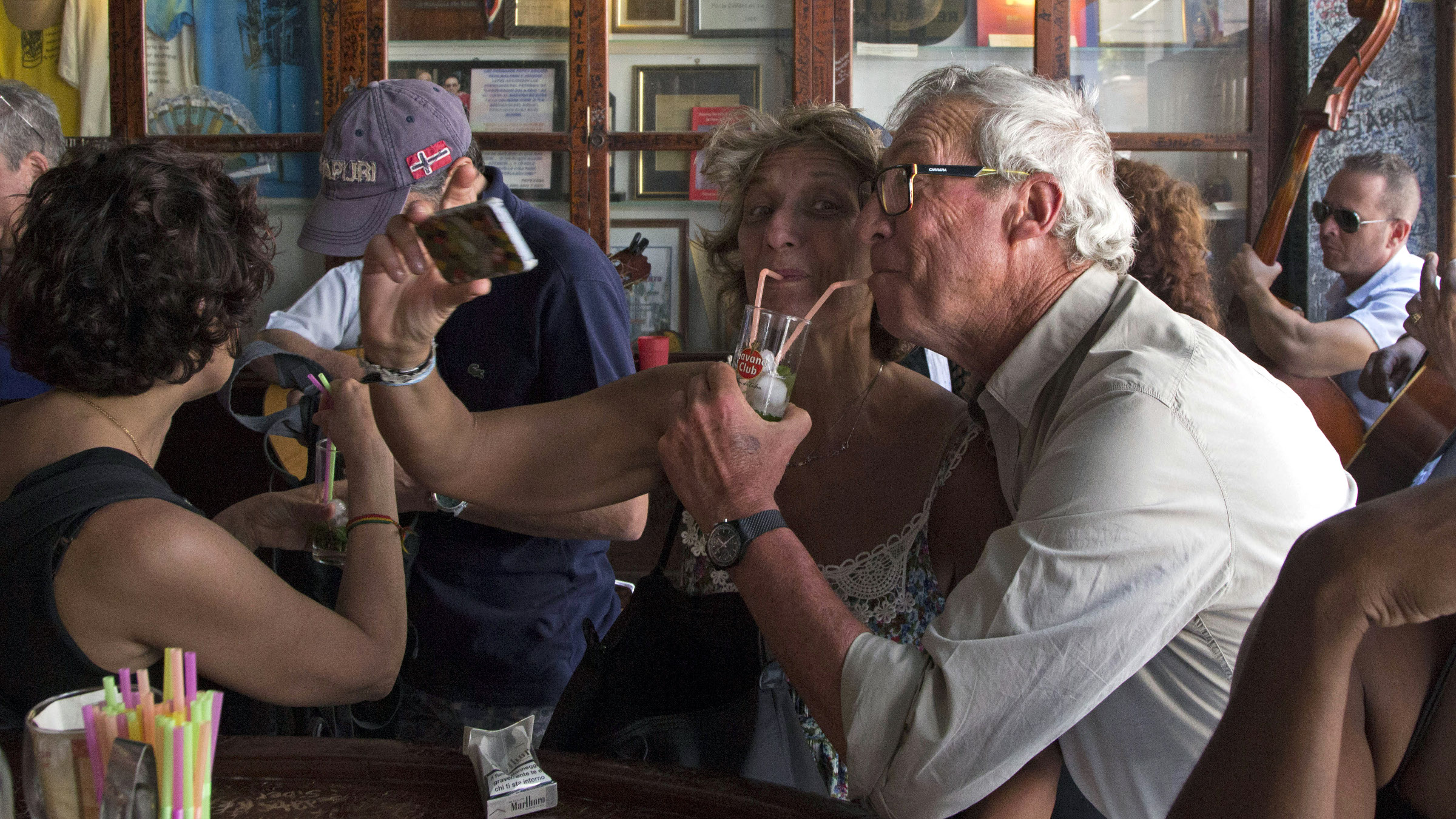 FILE - This Sunday, March 22, 2015 file photo shows tourists taking pictures of themselves as they drink a cocktail at the Bodeguita del Medio Bar frequented by the late American novelist Ernest Hemingway, in Old Havana, Cuba. Tourists trying to dine at high-end private restaurants are often struggling to find an empty table these days, and it's practically impossible to get a room at Havana's best hotels.