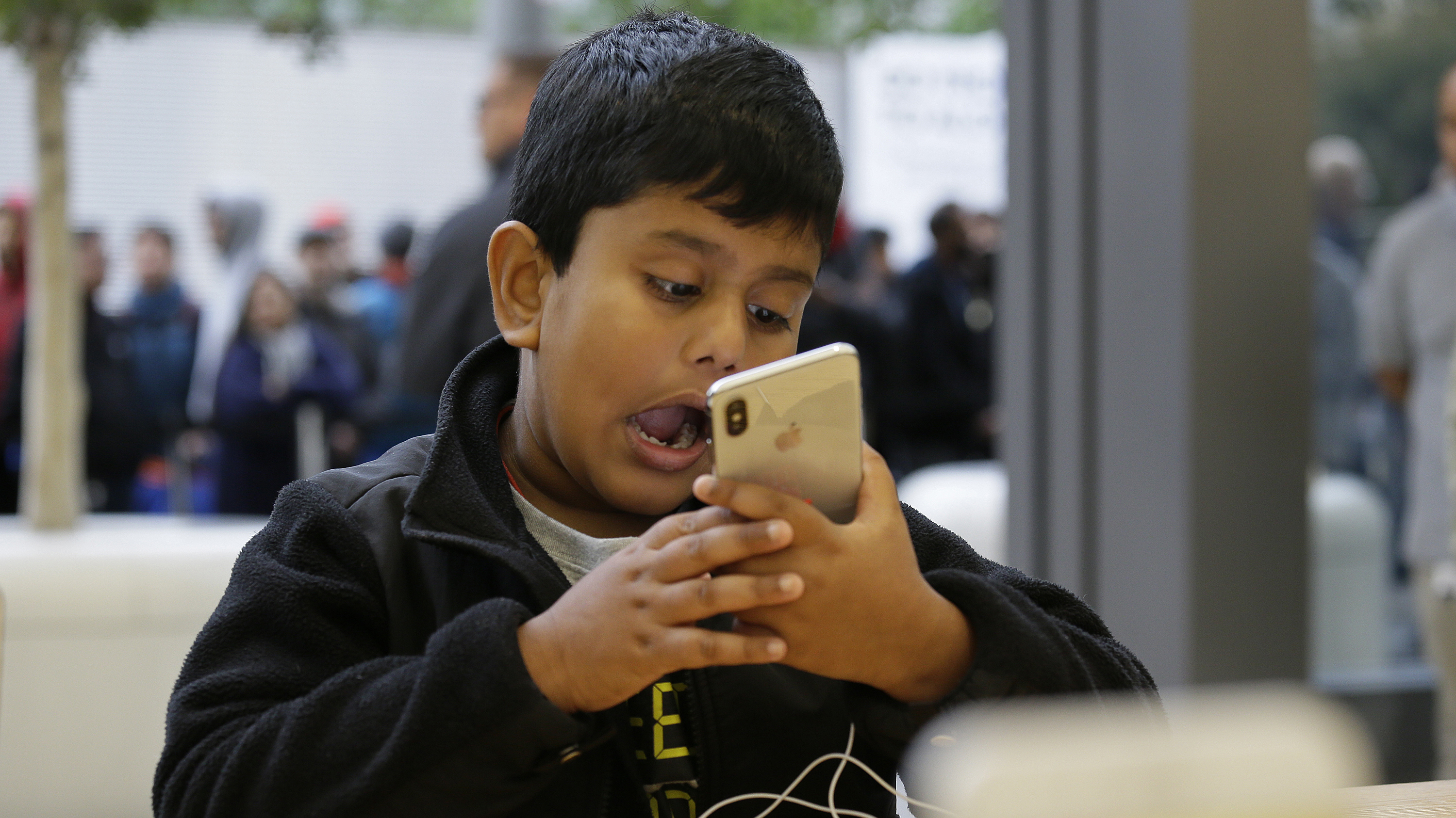 Aadhyan Vaka, 6, of Plainsboro, N.J., makes faces while using the animoji feature of the new iPhone X at the Apple Union Square store Friday, Nov. 3, 2017, in San Francisco. The iPhone X's lush screen, facial-recognition skills and $1,000 price tag are breaking new ground in Apple's marquee product line. Now, the much-anticipated device is testing the patience of consumers and investors as demand outstrips suppliers' capacity. (AP Photo/Eric Risberg)