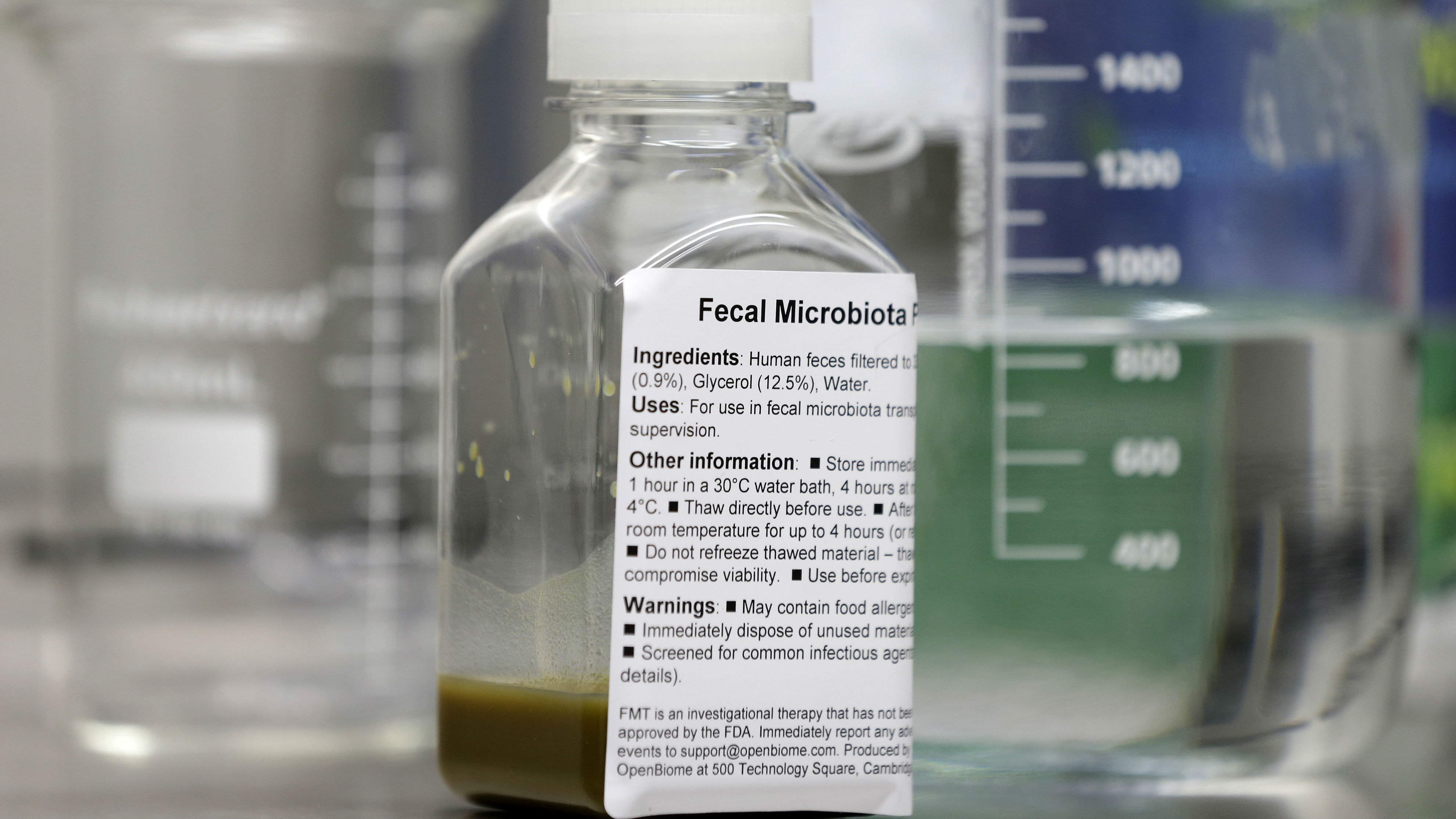In this Thursday, June 19, 2014 photo, a bottle containing human fecal matter solution sits in an OpenBiome laboratory, in Medford, Mass. Fecal transplants pose a unique challenge for the Food and Drug Administration, which has been trying to confirm the safety of the new therapy by regulating it as an experimental drug.