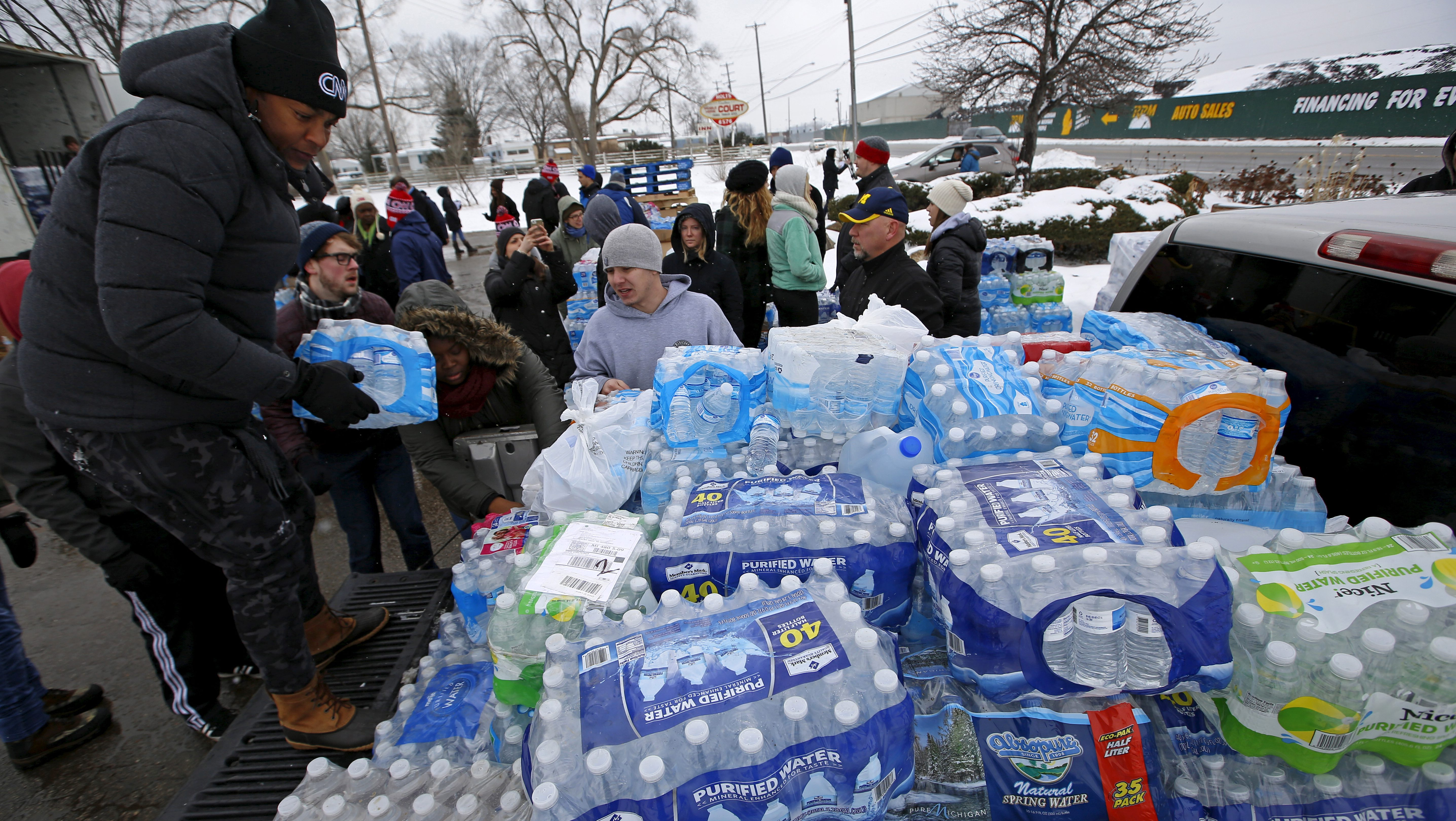 Volunteers distribute bottled water to help combat the effects of the crisis when the city's drinking water became contaminated with dangerously high levels of lead in Flint