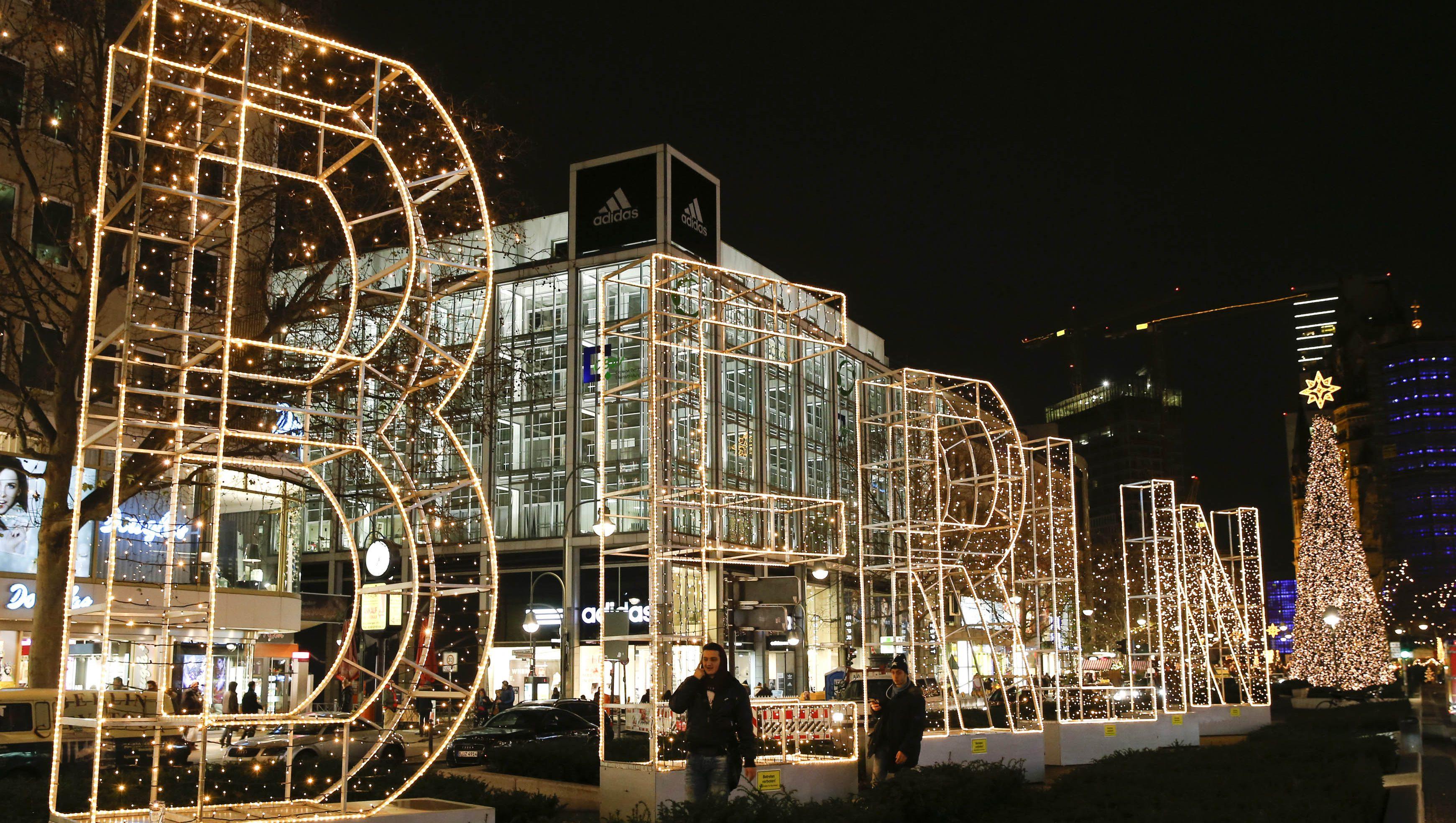 People walk past Christmas illuminations at the main shopping street Kurfuerstendamm in Berlin, Germany,