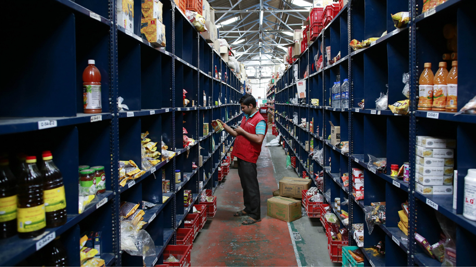 An employee scans a package for an order at a Big Basket warehouse on the outskirts of Mumbai November 4, 2014. Put off by snarled city traffic and a shortage of parking, more Indians are shopping for groceries online, helping e-tailers like Bigbasket.com and Localbanya.com turn in profits while supermarkets are struggling. Picture taken November 4. To match INDIA-INTERNET/RETAIL