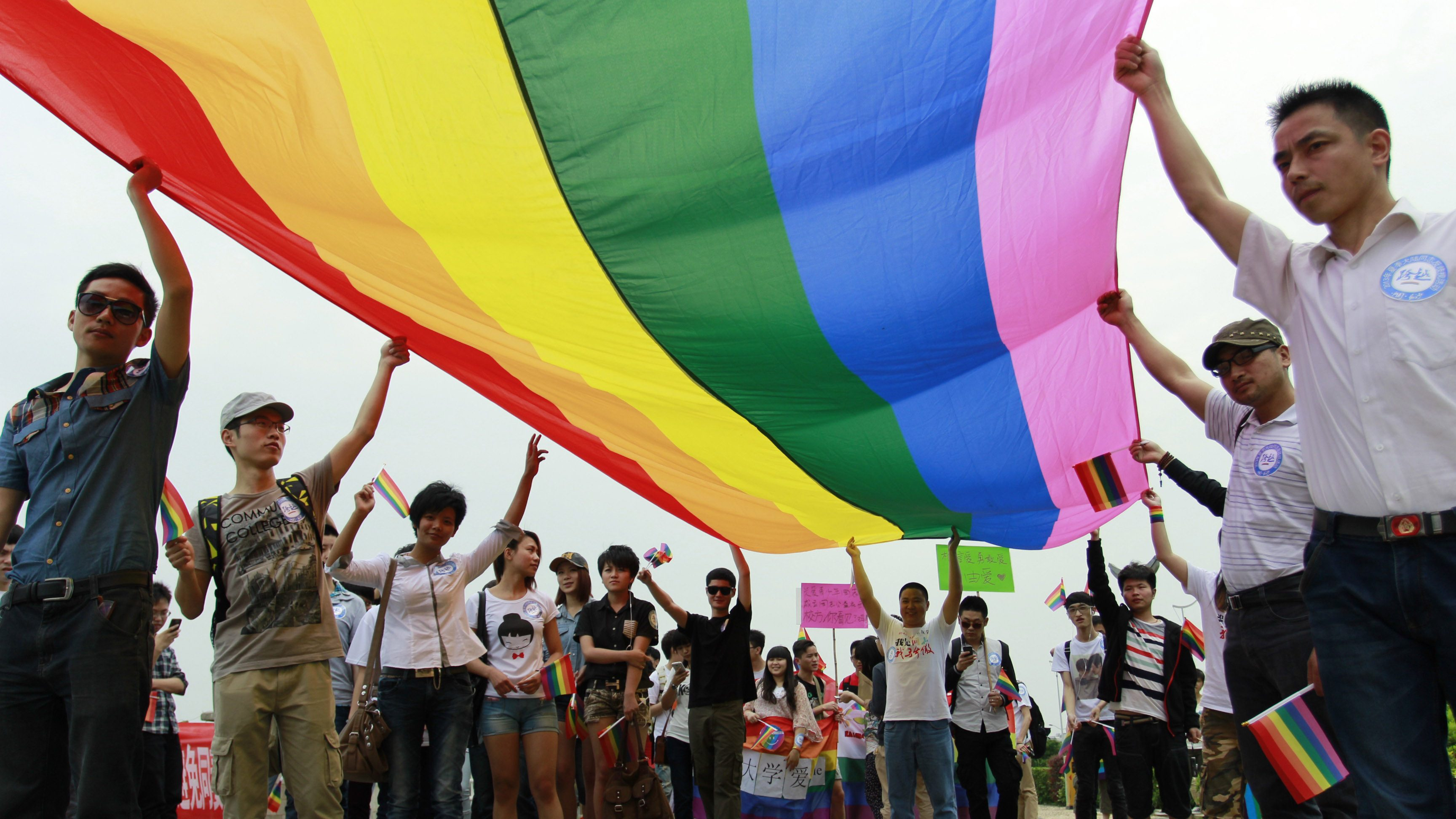 Activists brandishing a rainbow flag attend a gay pride procession in Changsha in South China's Hunan province, 17 May 2013. According to reports, around a hundred protesters attended a gay pride march calling for understanding and tolerance of sexual minorities.