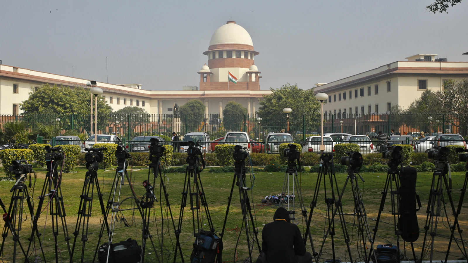 A television journalist sets his camera inside the premises of the Supreme Court in New Delhi February 18, 2014. India's Supreme Court commuted death sentences on three men for involvement in the killing of former prime minister Rajiv Gandhi to life imprisonment on Tuesday because of an 11-year delay in deciding on their petitions for mercy. Gandhi was killed by an ethnic Tamil suicide bomber while campaigning in an election in the southern Indian town of Sriperumbudur in May 1991.