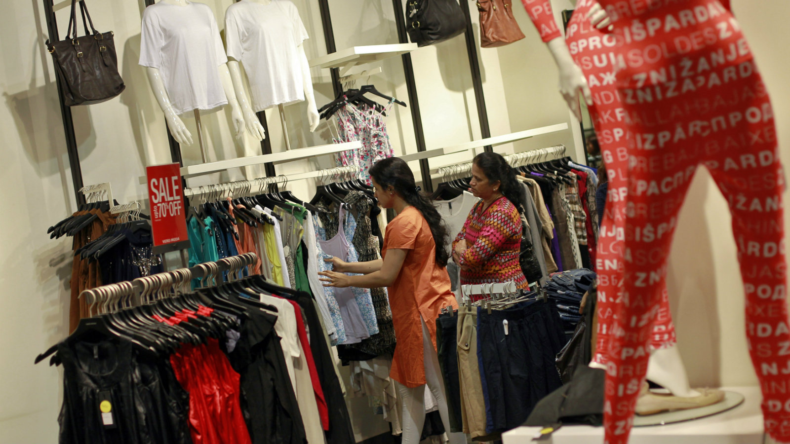 People shop for clothes at a store during a seasonal sale inside a shopping mall in Mumbai July 14, 2012. Asia's third-largest economy is growing at its slowest pace in nine years and sluggish consumer spending is forcing mall developers to scale back plans. It will take years for the glut of retail space conceived during headier times to be absorbed by tenants, even as India fine-tunes rules to make it easier for foreign shops to enter the country on their own, analysts say. Picture taken July 14, 2012. To match analysis INDIA-MALL/