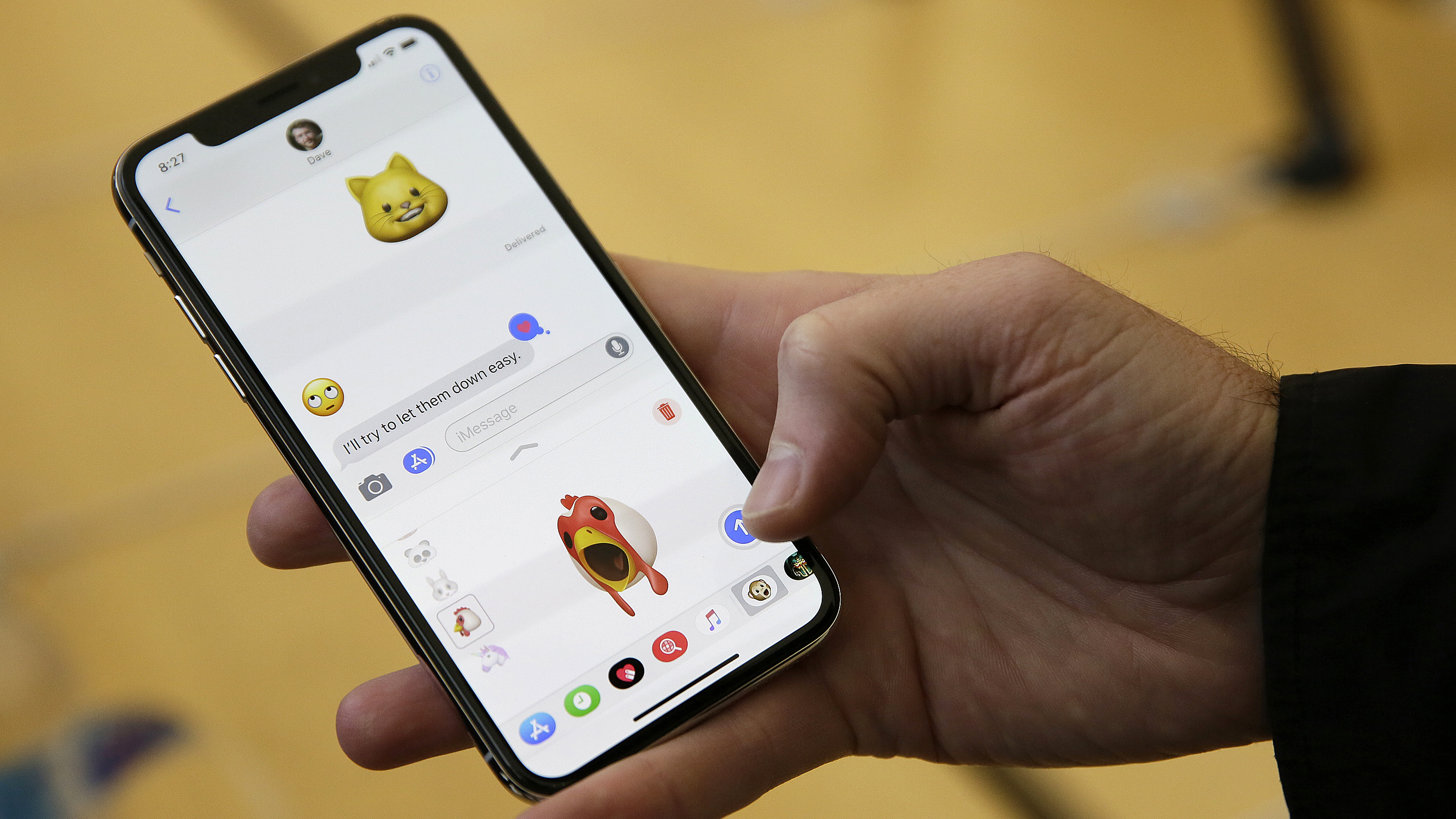 An Apple employee demonstrates the animoji feature of the new iPhone X at the Apple Union Square store Friday, Nov. 3, 2017, in San Francisco. Apple's iPhone X went on sale Friday, as the company scrambles to meet demand for a marquee device that sports a lush screen, facial-recognition skills and a $1,000 price tag. (AP Photo/Eric Risberg)