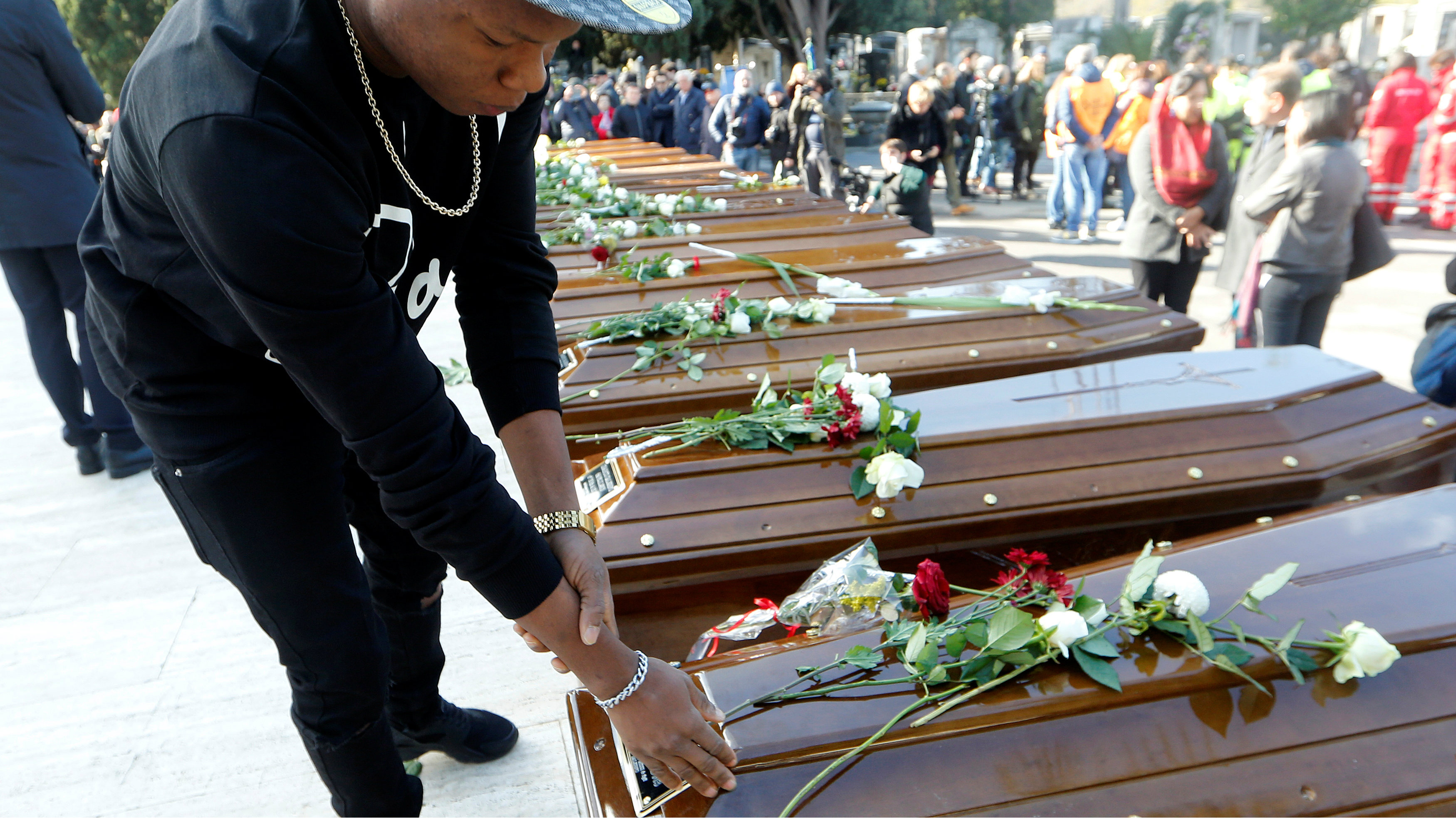 A man touches a coffin ahead of the funeral service for 26 Nigerian women who died last week while crossing the Mediterranean Sea, at the Salerno cemetery, Italy, November 17, 2017.
