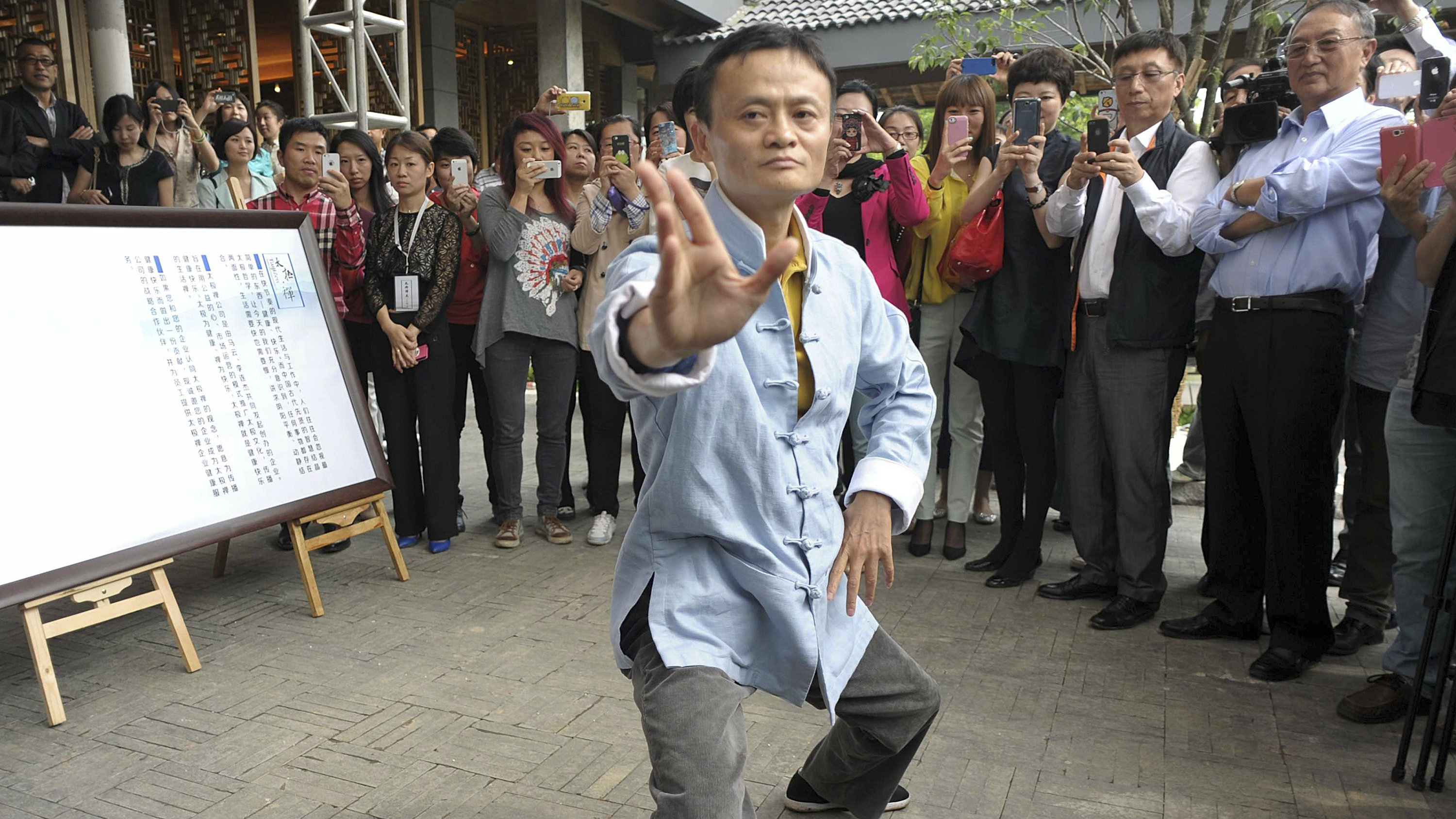 Jack Ma (C), chairman of China's largest e-commerce firm Alibaba Group, performs Tai Chi as guests and visitors take pictures and videos, at a opening ceremony of a Tai Chi school in Hangzhou, Zhejiang province May 10, 2013. Jack Ma stepped down as chief executive of Alibaba Group on Friday. The Tai Chi school was co-founded by Ma and Chinese action movie star Jet Li, local media reported.