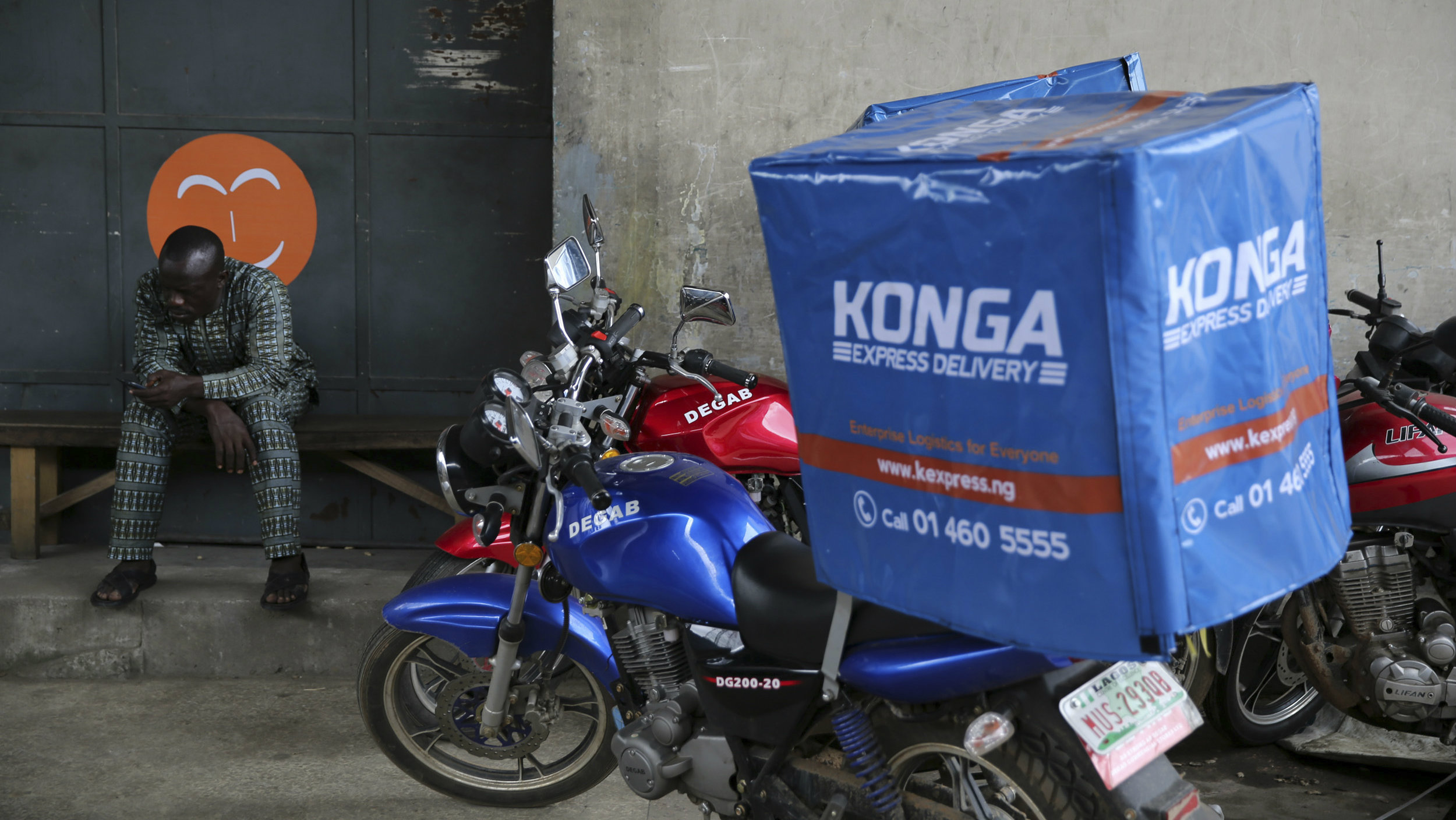 A man sits at the entrance to the warehouse of Konga online shopping company in Ilupeju district in Nigeria's commercial capital Lagos September 13, 2013.