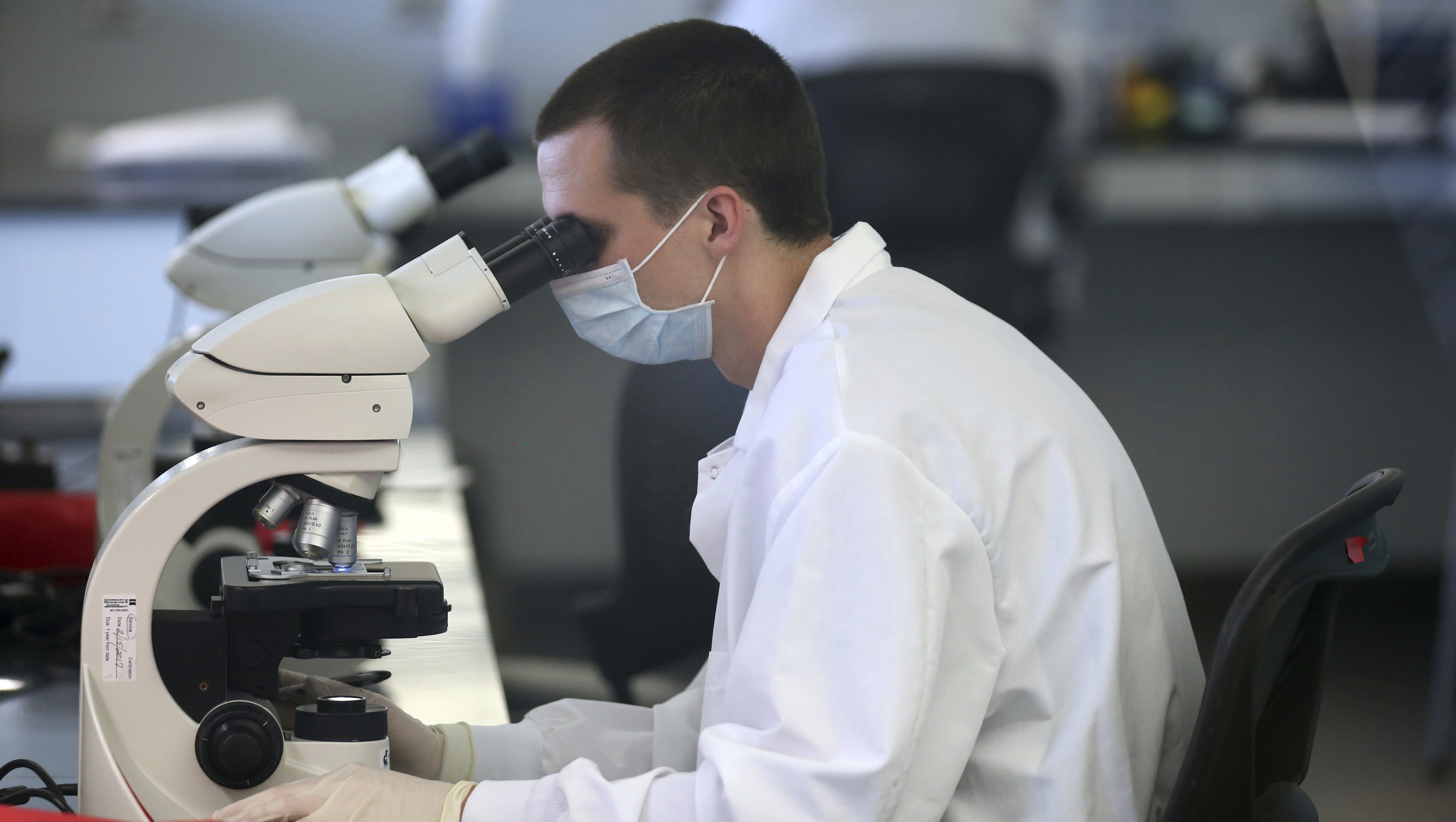 A forensic scientist looks through a microscope at the state crime lab, Thursday, July 6, 2017, in Taylorsville, Utah. Kidnapping victim Elizabeth Smart and Sen. Orrin Hatch, R-Utah, toured the new state crime lab Thursday. Smart is throwing her support behind Hatch's proposal that would speed up DNA testing at crime labs. (AP Photo/Rick Bowmer)